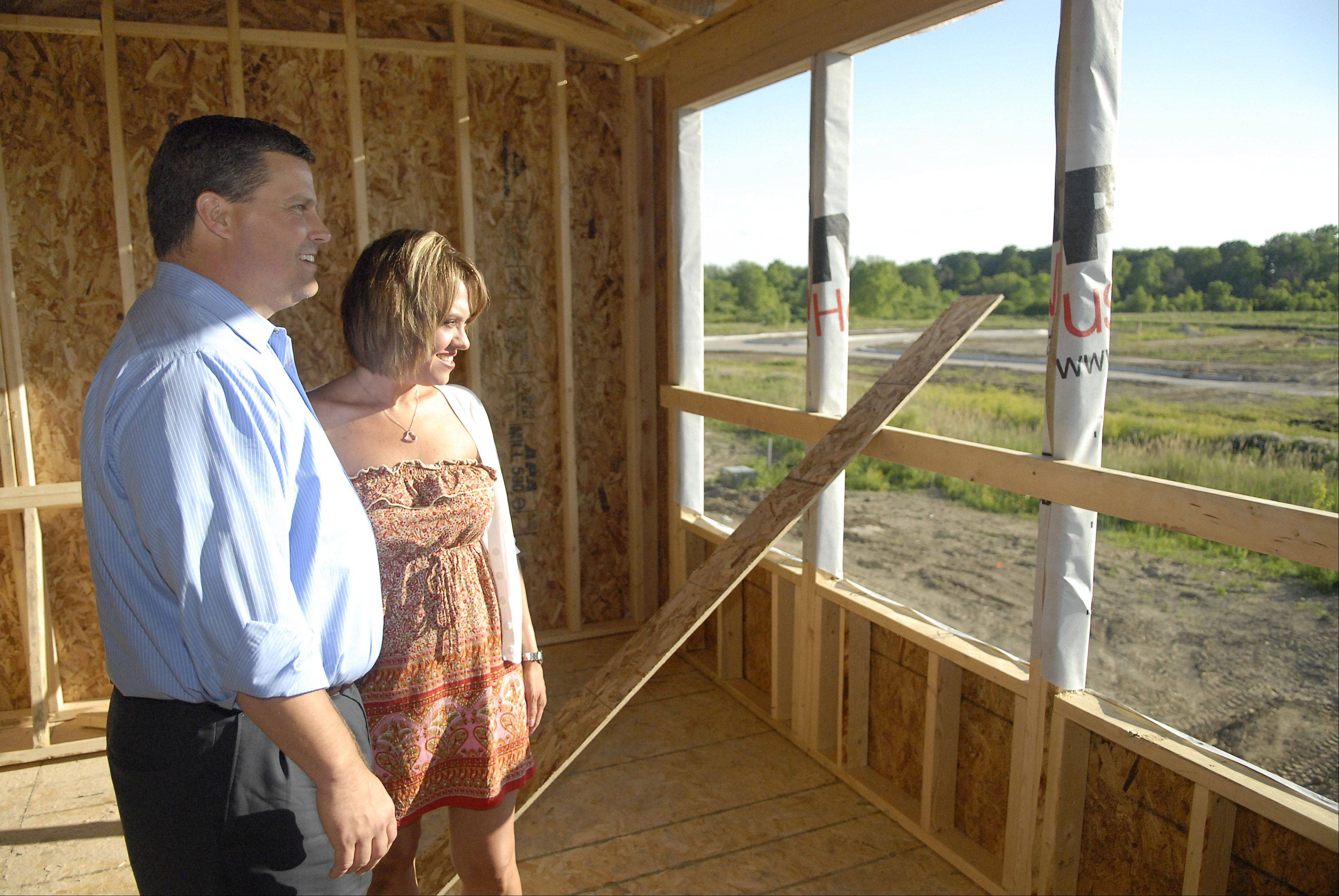 Michelle Lopez and her boyfriend, Peter Truschke, take in the view of their future master bedroom and seating area in the home they are having built in the Winchester Glen subdivision in Carpentersville. They expect it to be completed by August. The view includes a conservation area.
