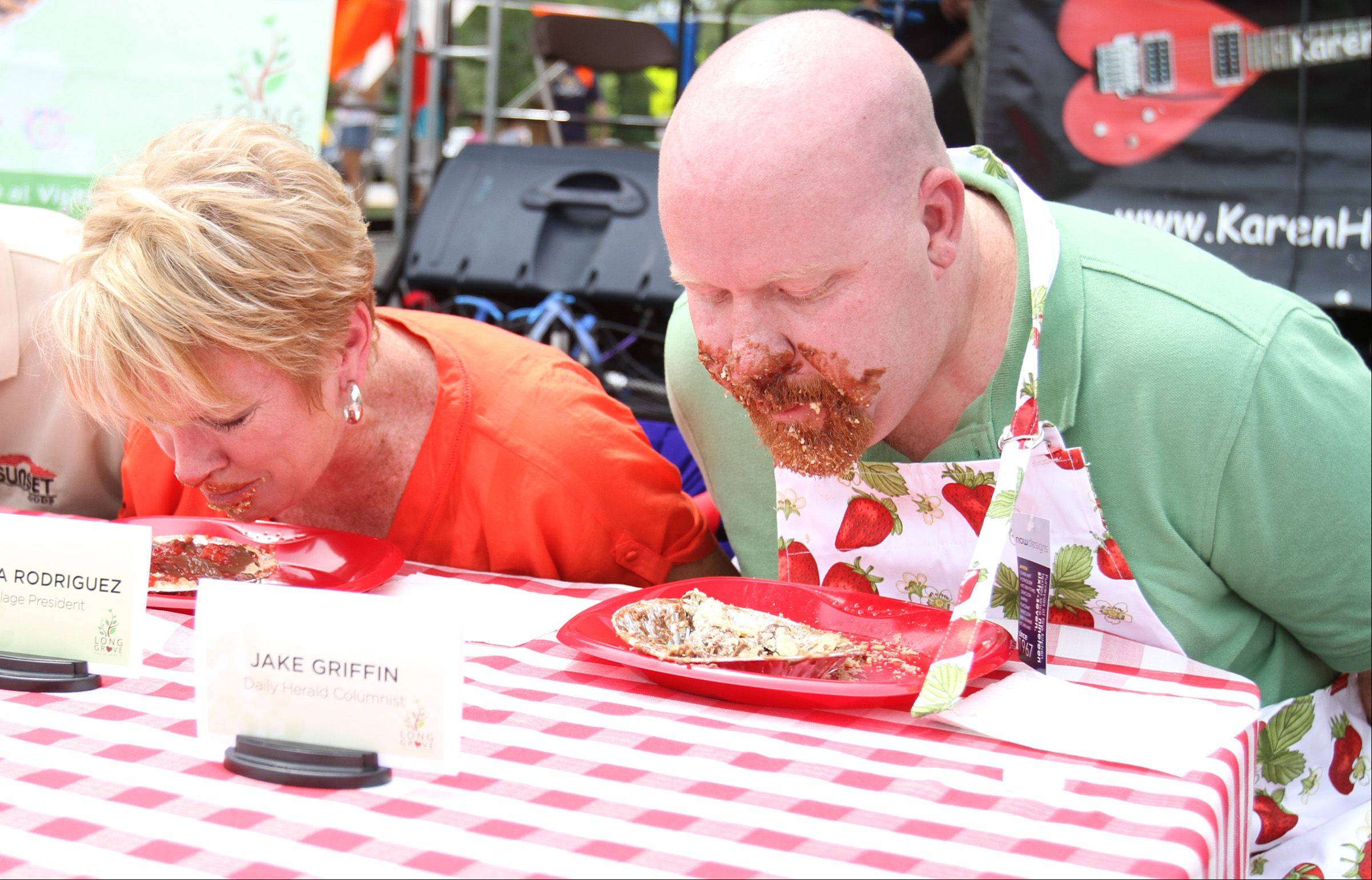 With their hands tied behind their backs, Daily Herald reporter Jake Griffin competes with Maria Rodriguez, Long Grove Village president, Ron Bernardi representing Sunset Foods, and John Garcia, ABC channel 7 anchor, in the celebrity division of Long Grove's pie-eating contest at the Long Grove Strawberry Festival on Saturday. The festival continues 10 a.m. to 6 p.m. Sunday.