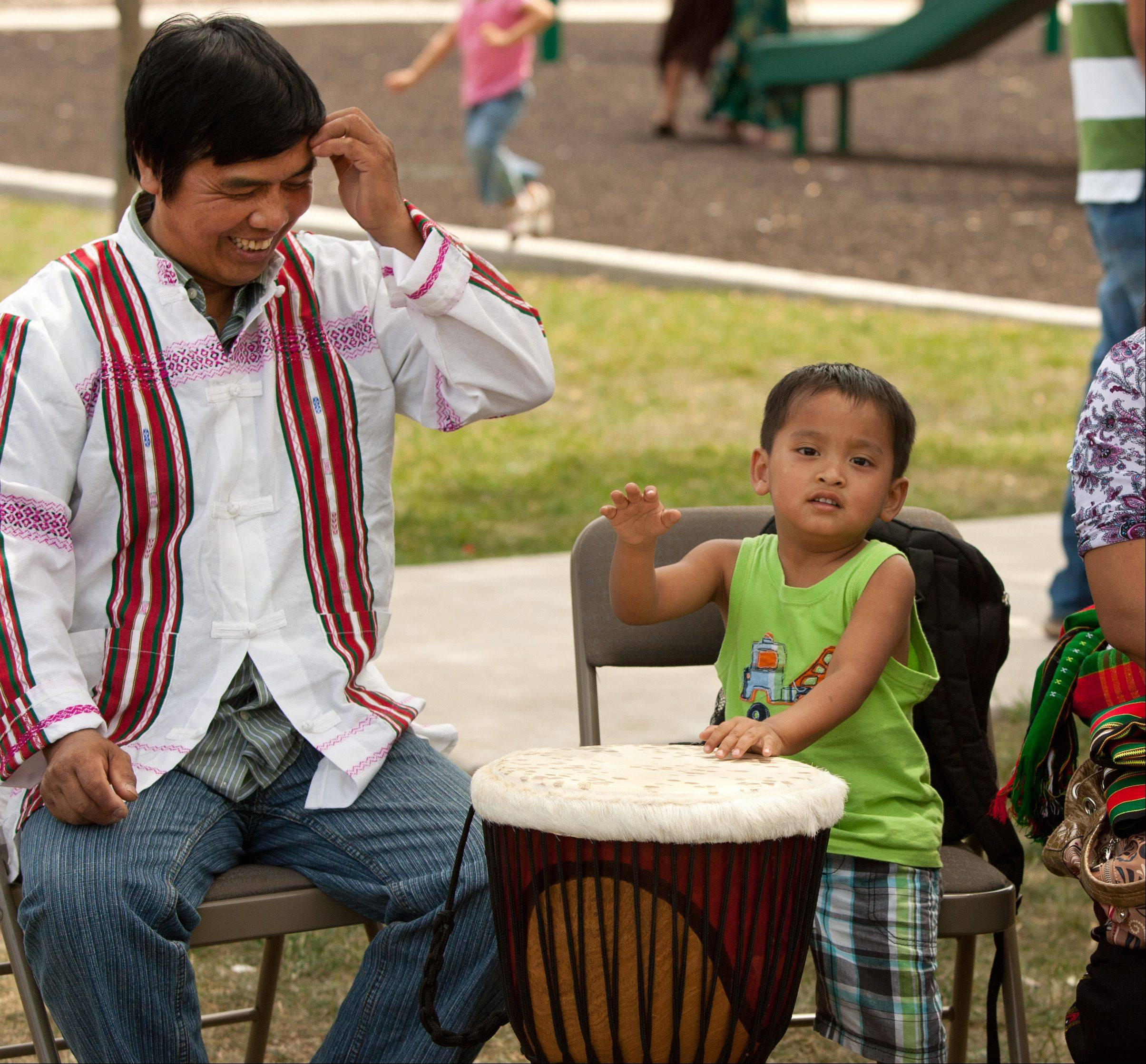 Pius Paucin, left, of Wheaton listens to Abraham Kapcinkhai, 3, of Glen Ellyn as the boy plays the Khuang drum Saturday in Wheaton at a picnic hosted by World Relief DuPage/Aurora and Exodus World Services. The picnic recognized World Refugee Day, which was June 20.