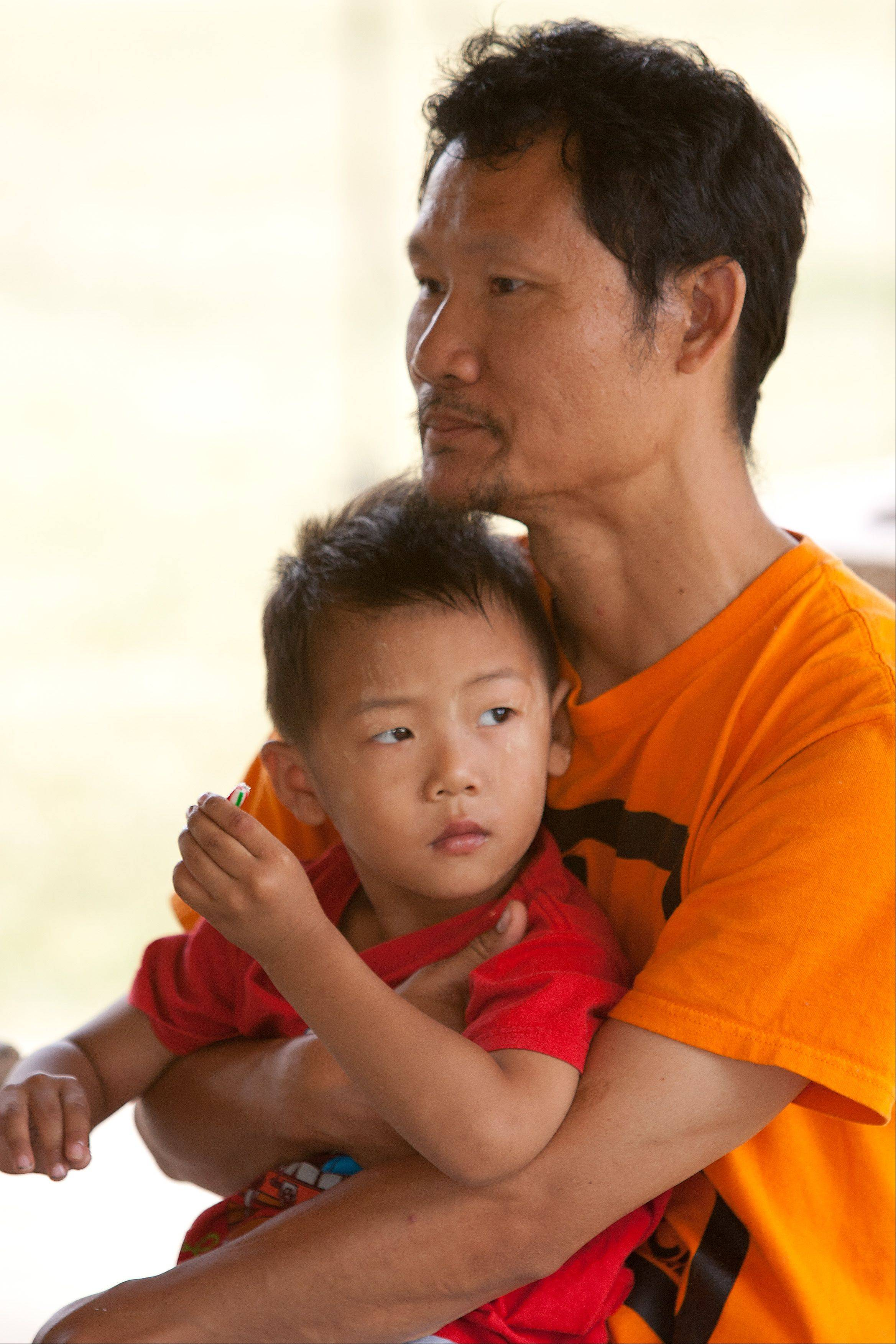 Soe Rah, a Wheaton resident and leader of the area's Karen Burmese community, holds his son, Saw Soe, 3, Saturday during a picnic hosted by World Relief DuPage/Aurora and Exodus World Service.