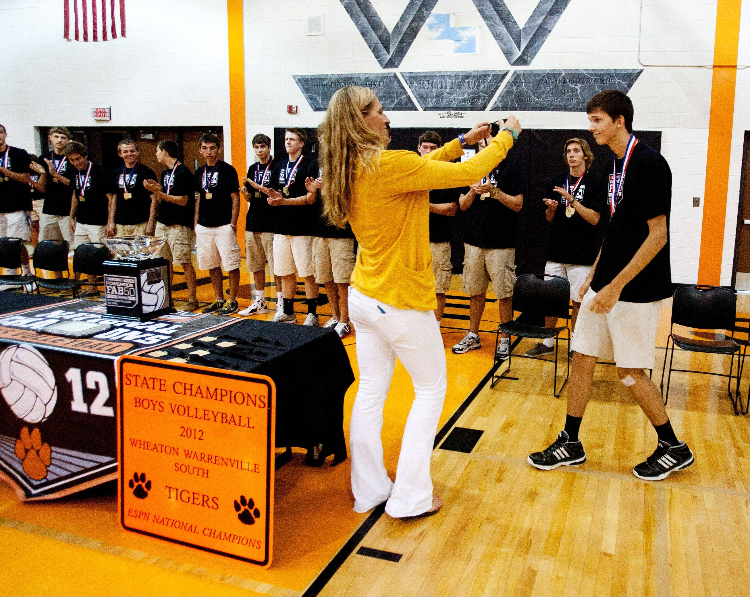 Kirstin Olsen of ESPNHS honors members of the Wheaton Warrenville South boys volleyball team with national championship medals Friday.
