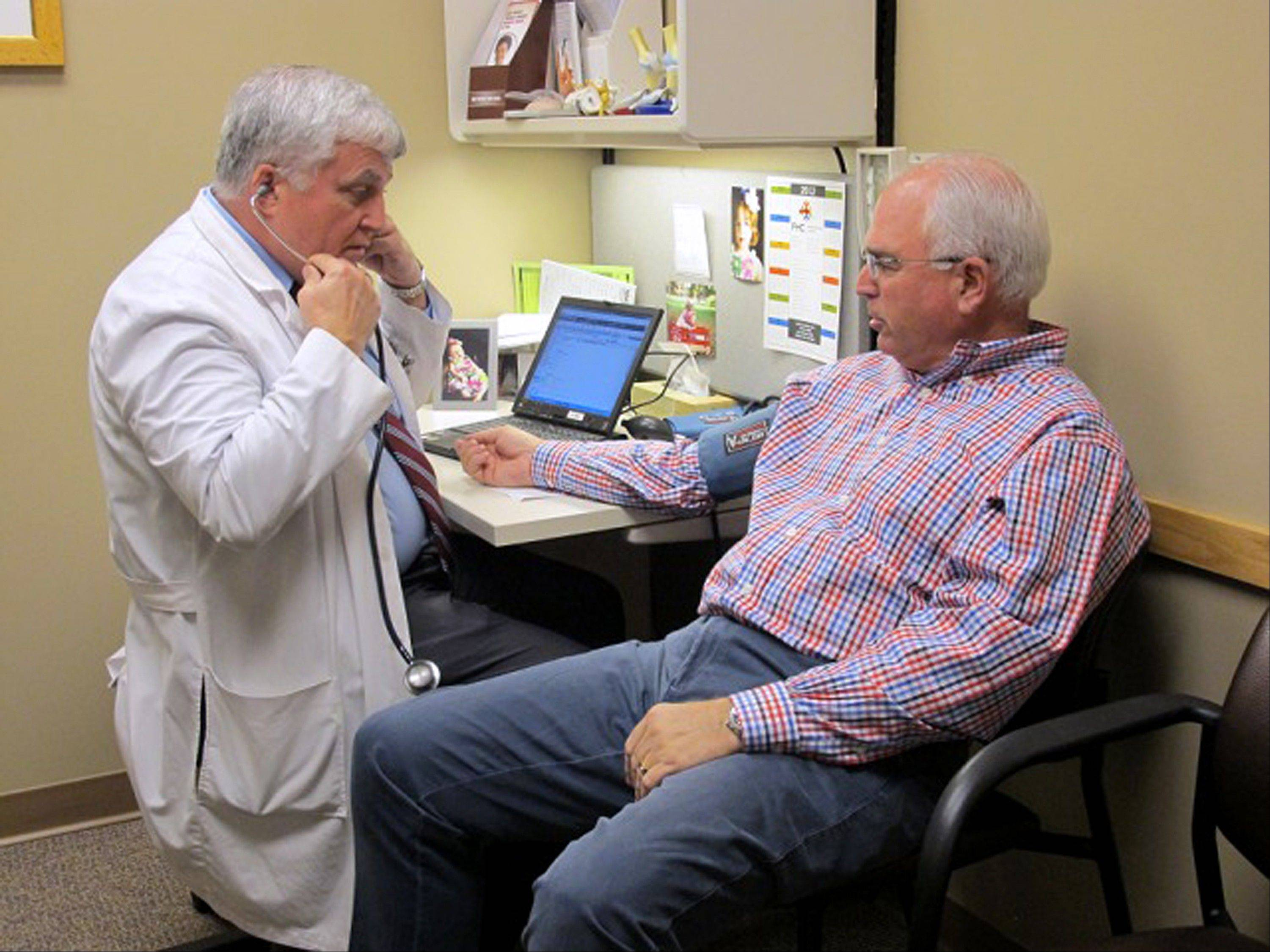 "Dr. Glen Stream prepares to examine patient Pete Forsyth in Spokane, Wash., on June 11. Health care spending has eased up recently, a welcome respite for government and corporate budgets. ""Far and away it is related to economic issues,"" Stream said. ""I see people who have medical conditions who I should be seeing every three months. They tell me they can only afford to come in every six months or once a year."""