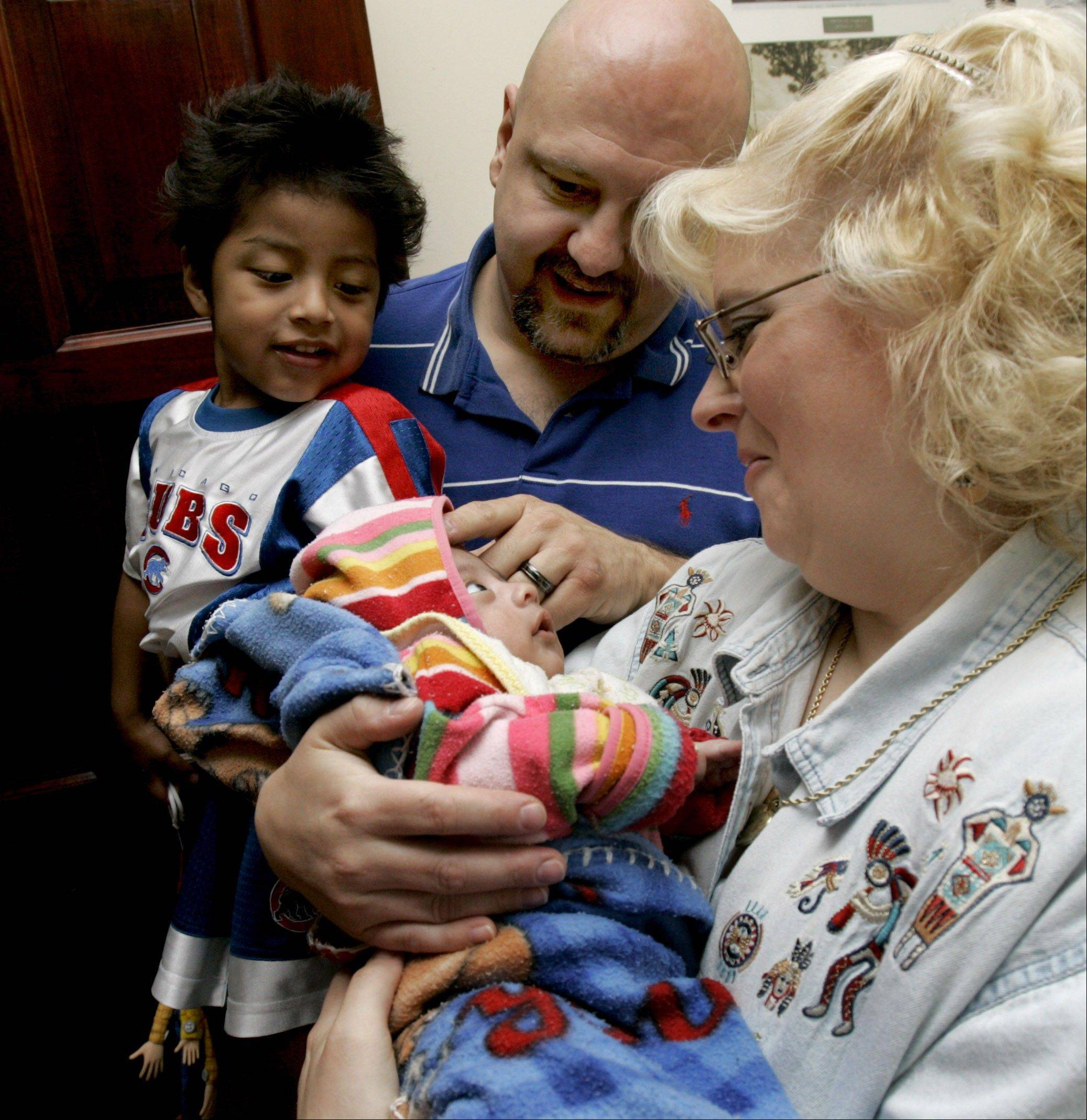 Bill and Kris Hull and son Myles meet their new son Clayton at a lawyer's office in Guatemala City. Bev Horne shot this photo during a 2006 series on international adoption.