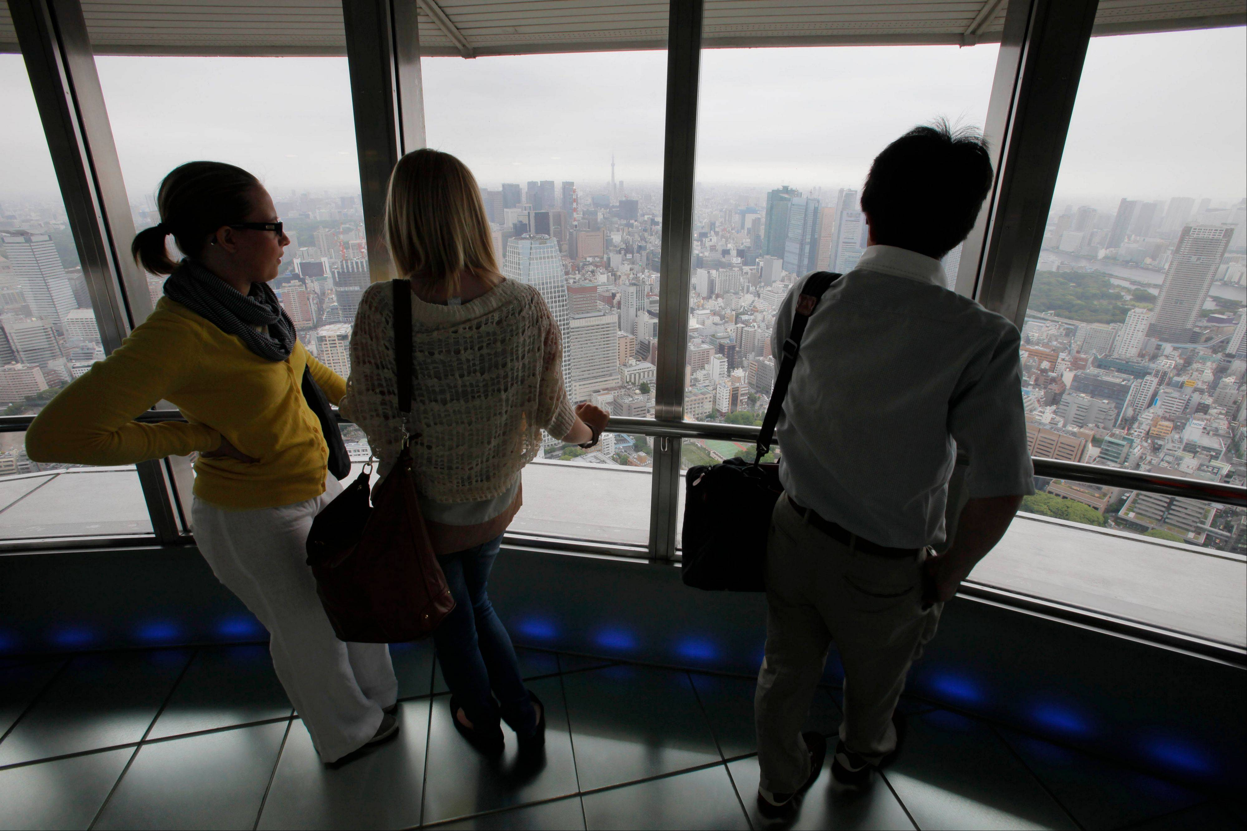 Visitors on the observation deck of Tokyo Tower in Japan. The Tokyo tourist experience is more affordable than the perception of an expensive city might suggest.