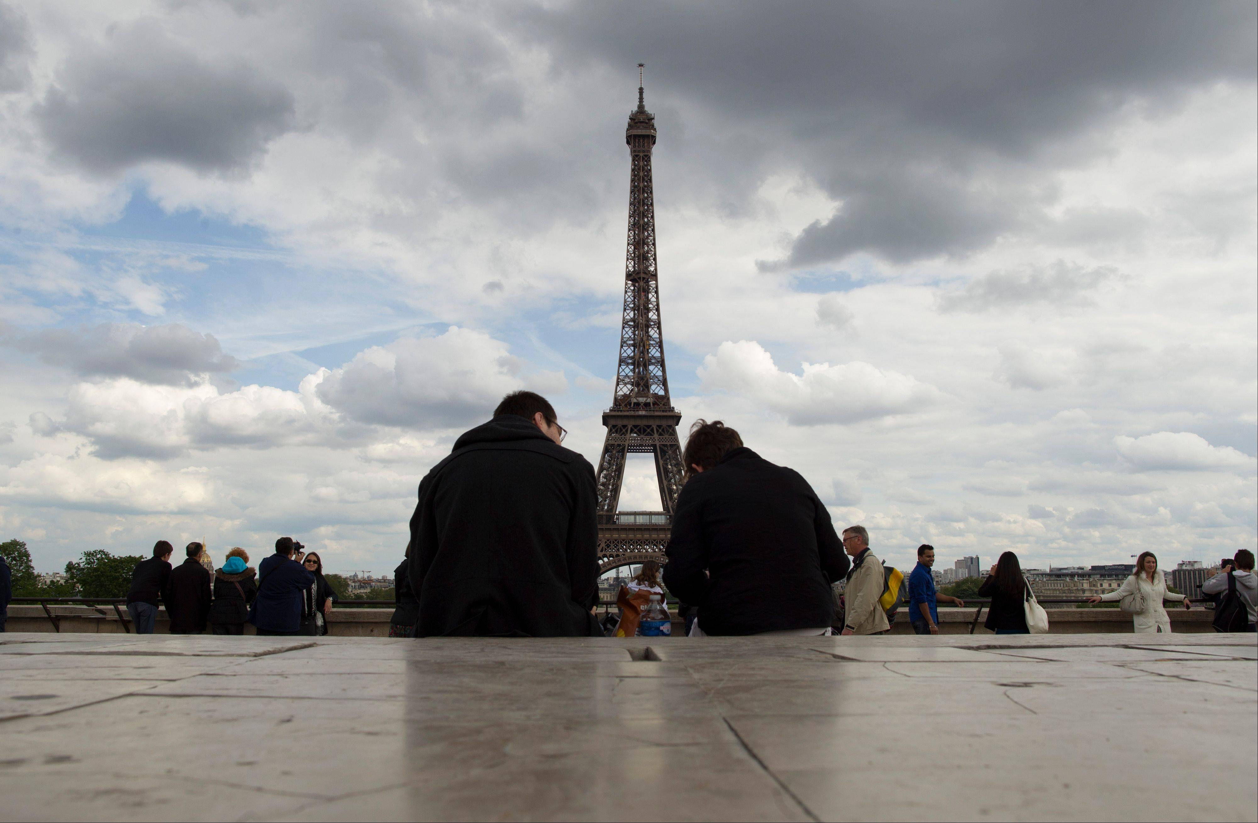 Visitors admire the view of the Eiffel Tower in Paris.