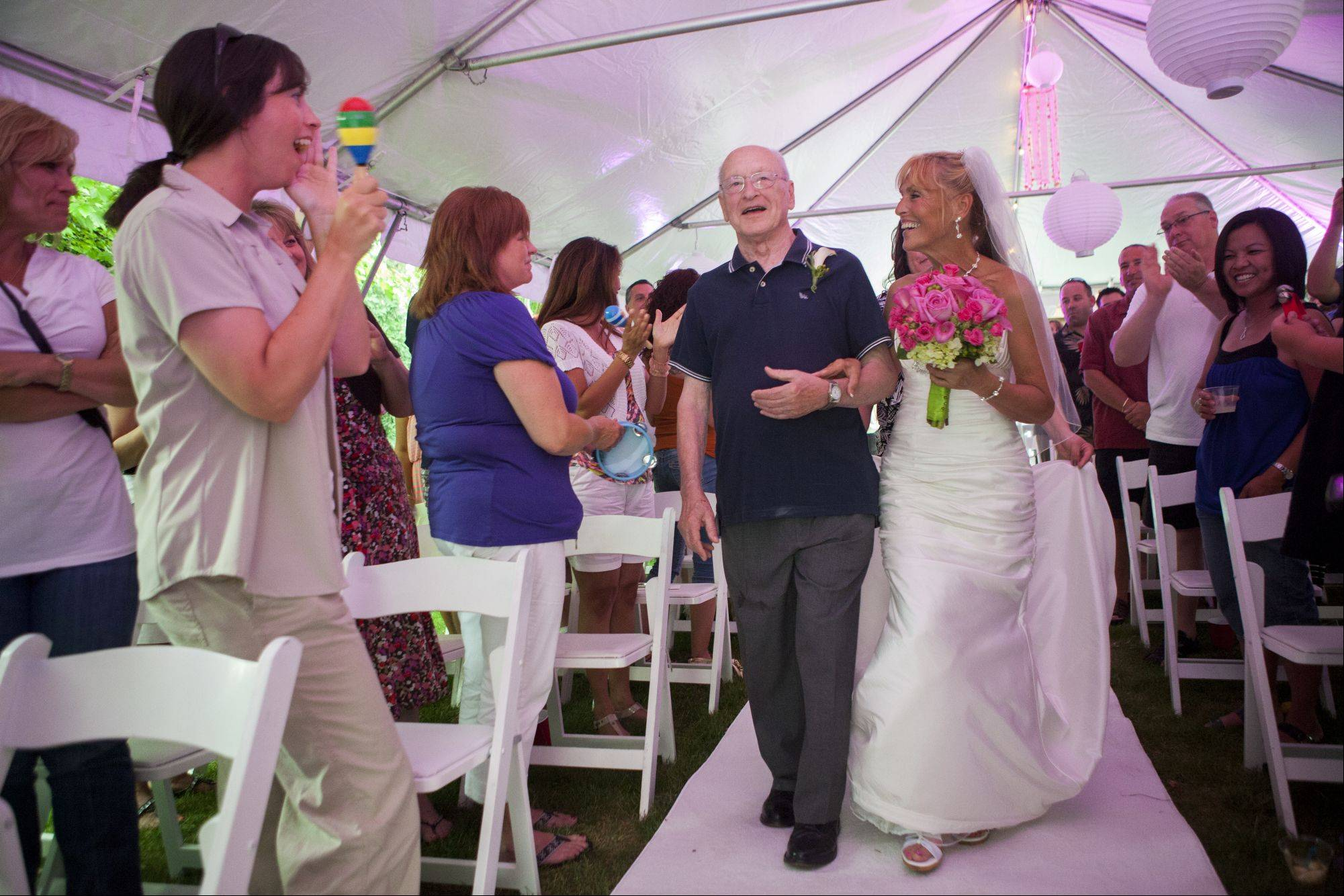 Libby Watkins and her father, retired Cook County Judge Edward Fiala, walk down the aisle, which was set up only minutes before the flash mob wedding Sunday night in Schaumburg.