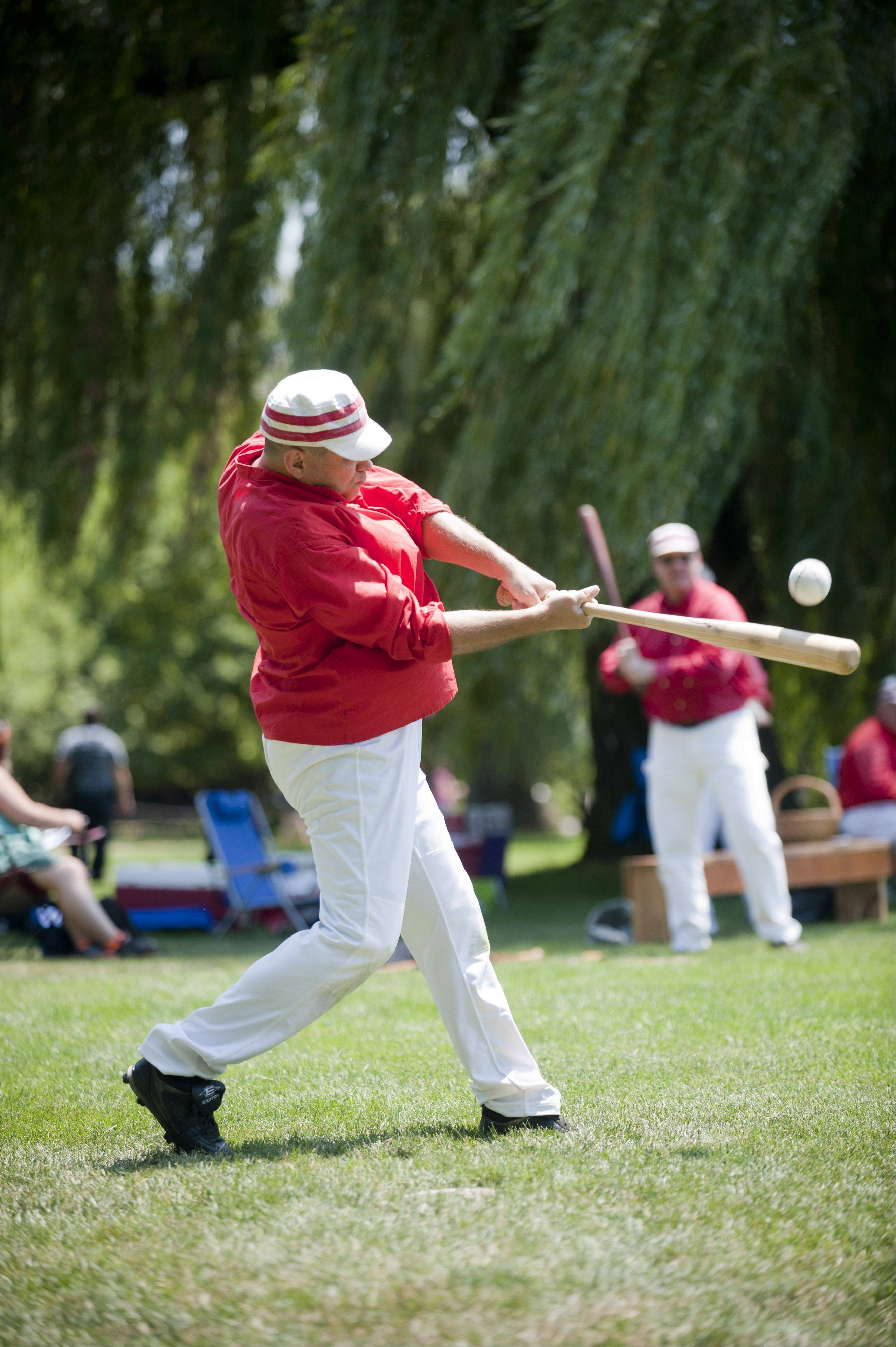 "A member of the DuPage County Plowboys hits a double during an old time baseball game at Cantigny Park in Wheaton on Sunday. The event featured ""base ball"" teams competing under the sport's Civil War-era rules."