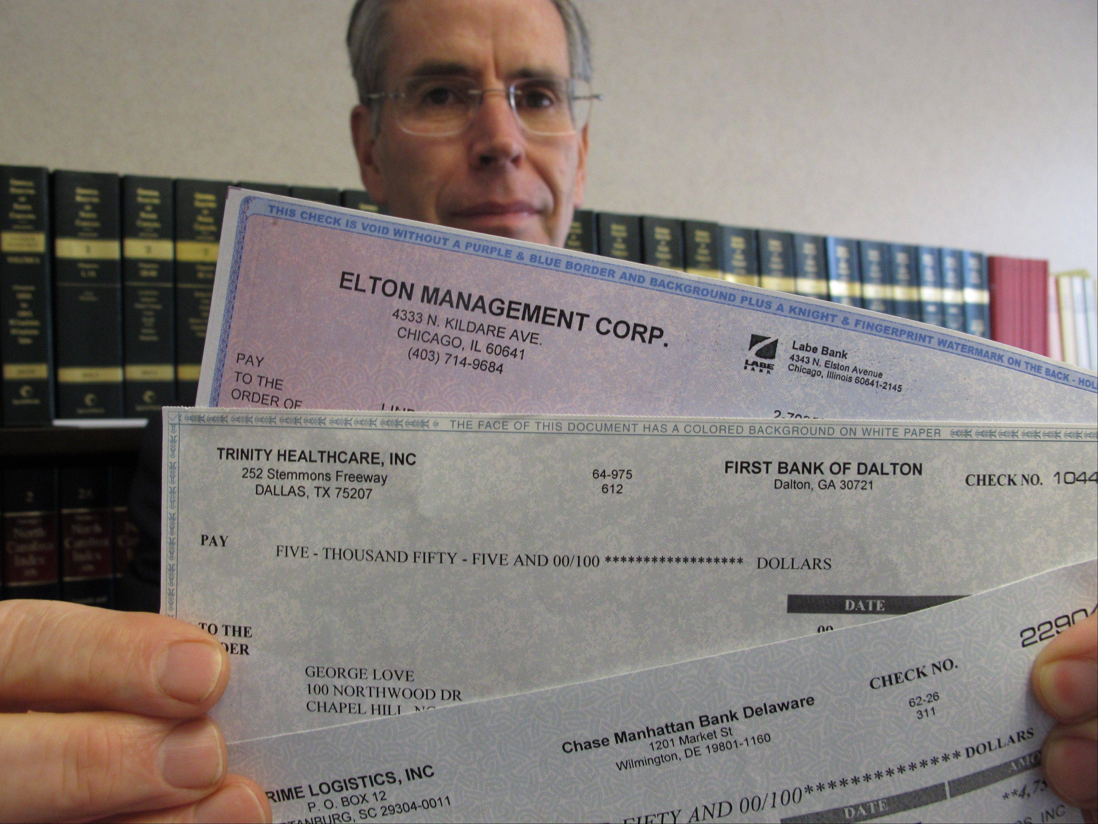 Assistant Attorney General David Kirkman on June 11 holds checks of the type often received by targets in his Raleigh, N.C., office. The recipient forwarded them to his office. Kirkman said sometimes the checks carry the names and account numbers of legitimate companies, and by the time a bank confirms they're bogus, the victim has usually sent the amount to the scammer via wire and ends up on the hook for the money. He also said the amount of money swindled from North Carolinians by these scams has doubled in the past year.