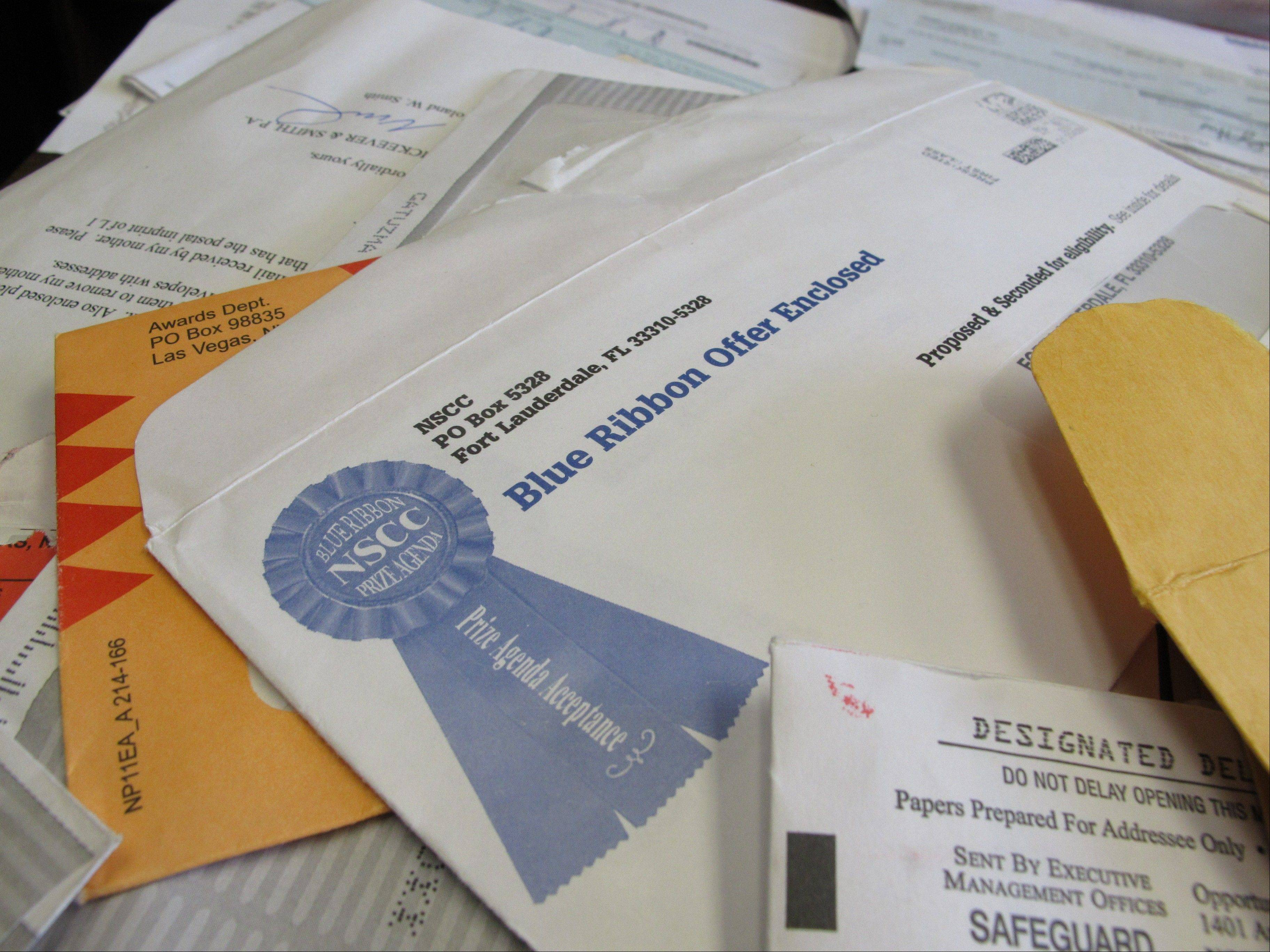 Piles of official-looking sweepstakes and other mailings are spread on a table at the North Carolina attorney general's office in Raleigh, N.C., on June 11. Officials say elderly people lose nearly $3 billion a year to such fraud.
