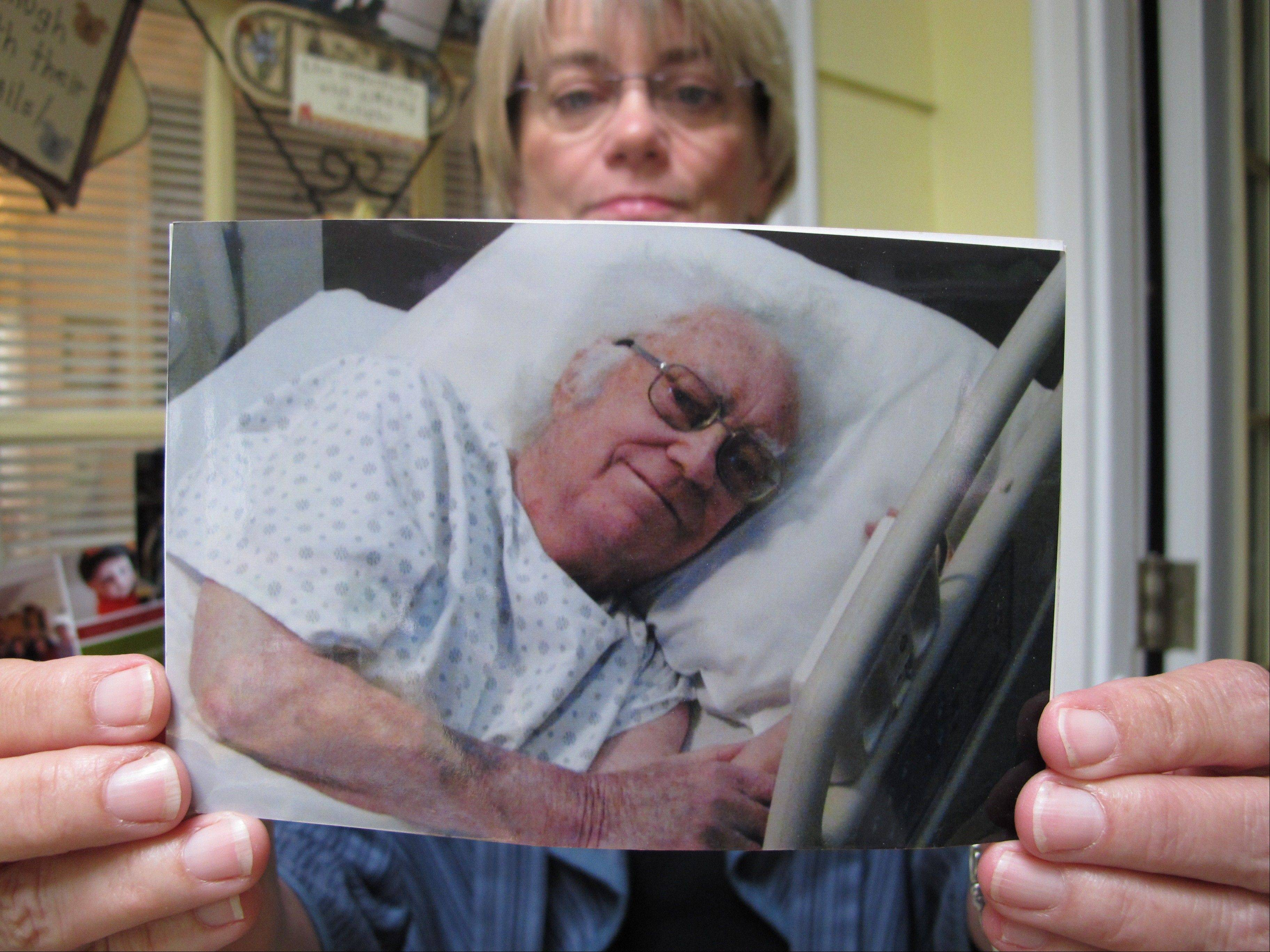 At her Cary, N.C., home, Donna Parker on June 18 holds a picture of her father, Charles, shortly before his death in February 2012. She and her siblings spent years extricating their parents from an international sweepstakes scam.