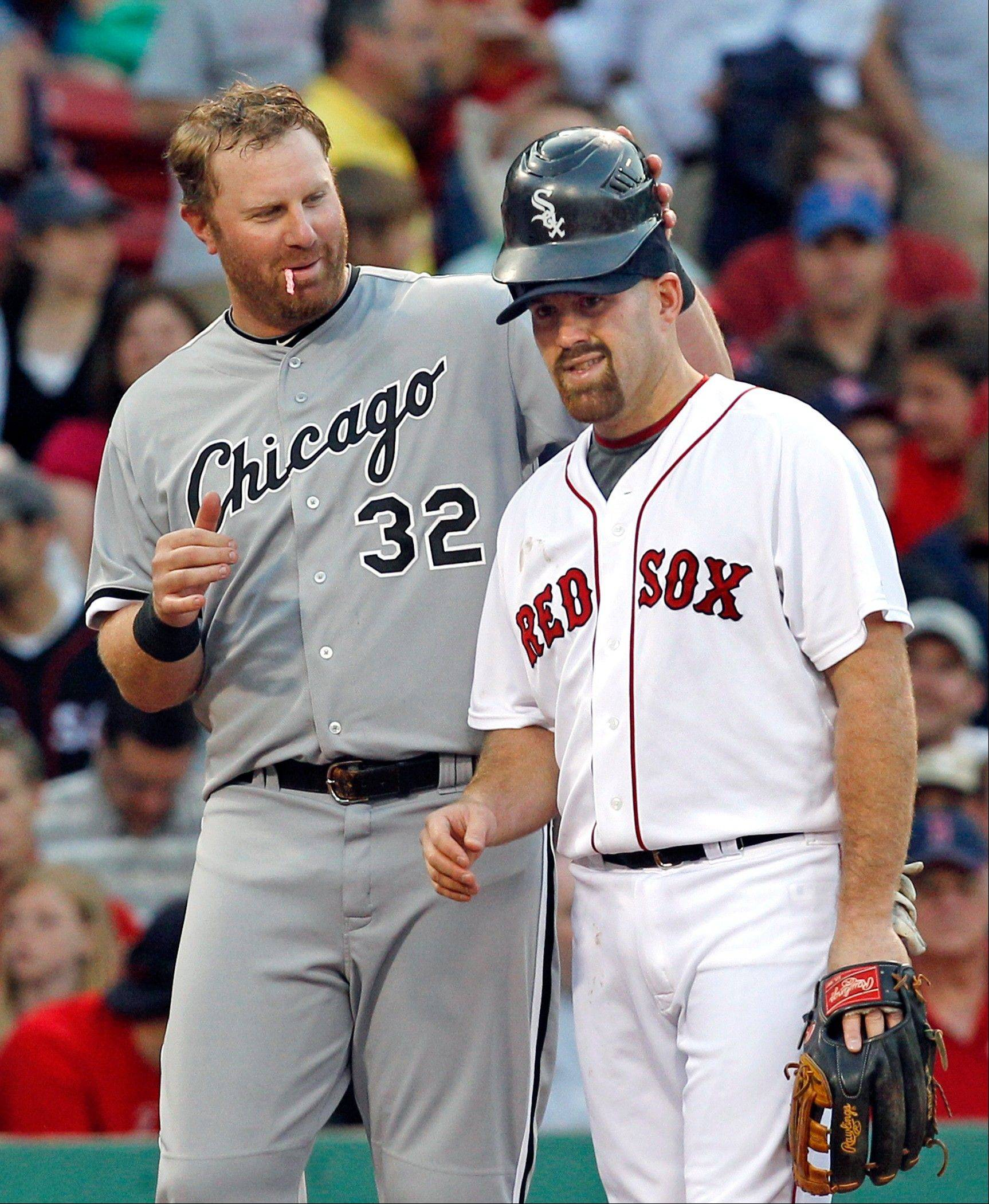 White Sox slugger Adam Dunn playfully puts his batting helmet on Kevin Youkilis during a game last year at Fenway Park. Youkilis will now put on his own White Sox uniform after being acquired Sunday in a trade with the Boston Red Sox.
