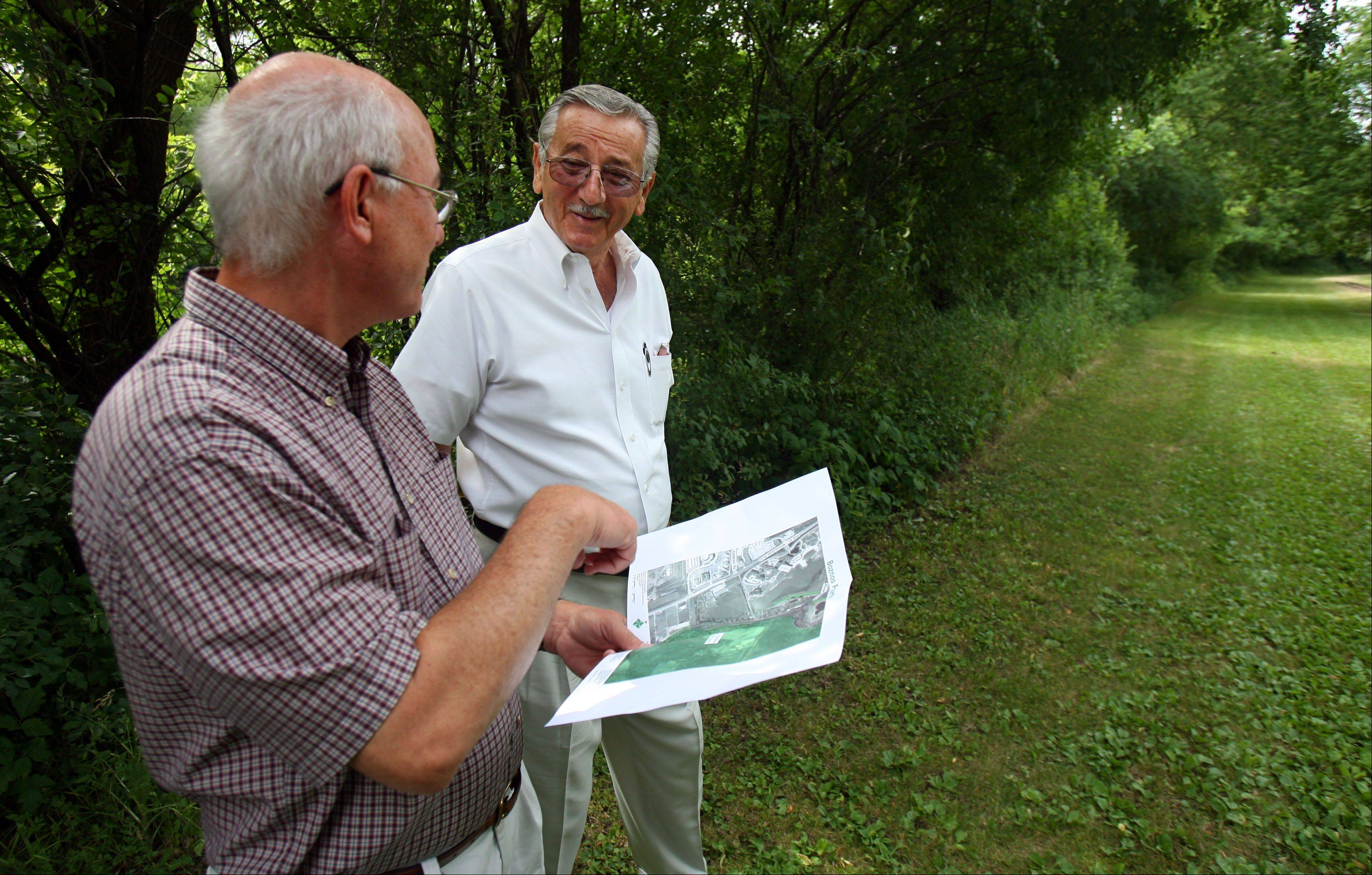 Tom Hahn of the Lake County Forest Preserve District, left, and land owner Gus Boznos stand on a 1,500-foot stretch of land behind the Par King Skill Golf course near Lincolnshire that is needed to finish the Des Plaines River Trail.