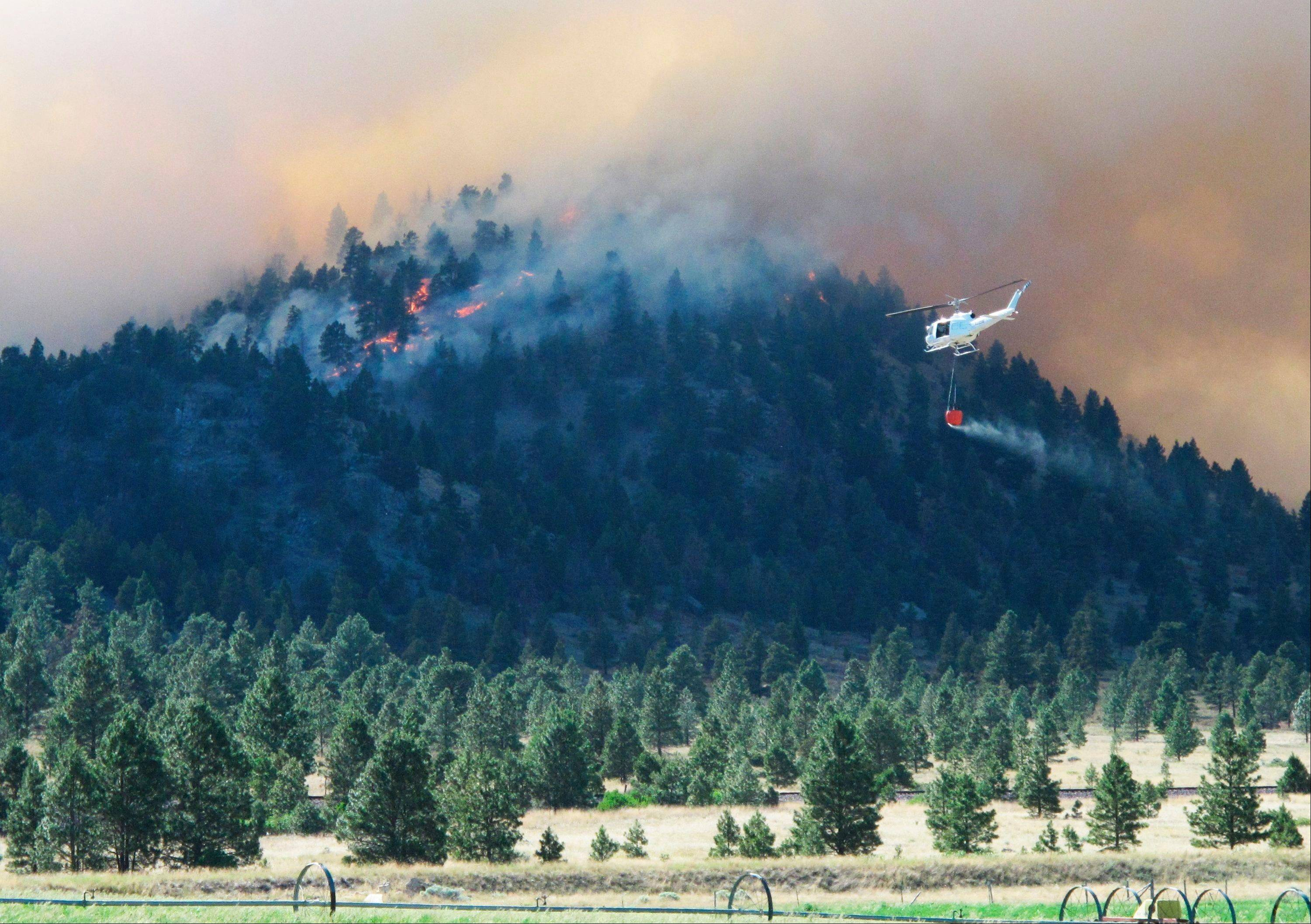 A helicopter heads toward a burning ridge Monday, north of Helena, Mont. Scorching heat and high winds have caused wildfires to break out across southwestern Montana, forcing the evacuation of more than 200 homes.
