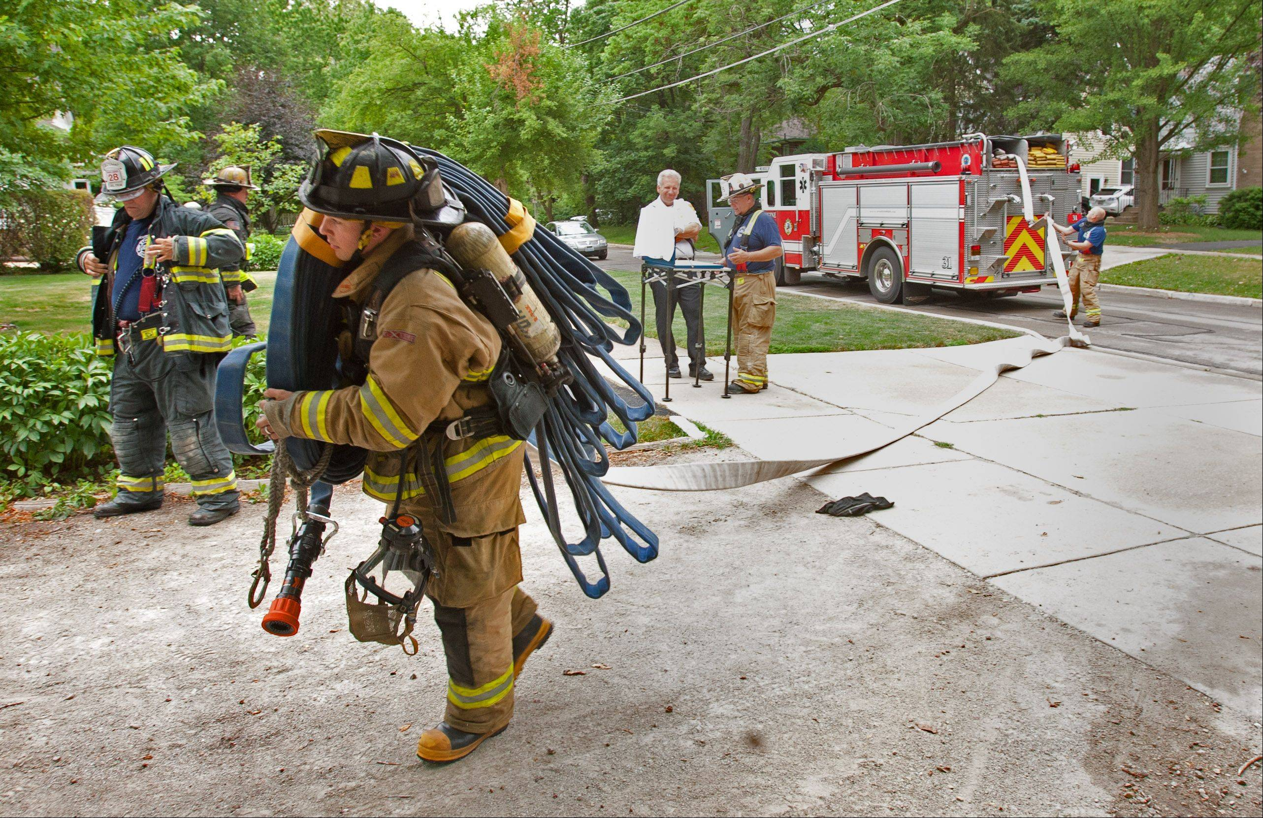 Christian Dagenais of the Winfield Fire District rolls out hose at a training exercise among the Carol Stream, West Chicago, Winfield and Wheaton fire departments.