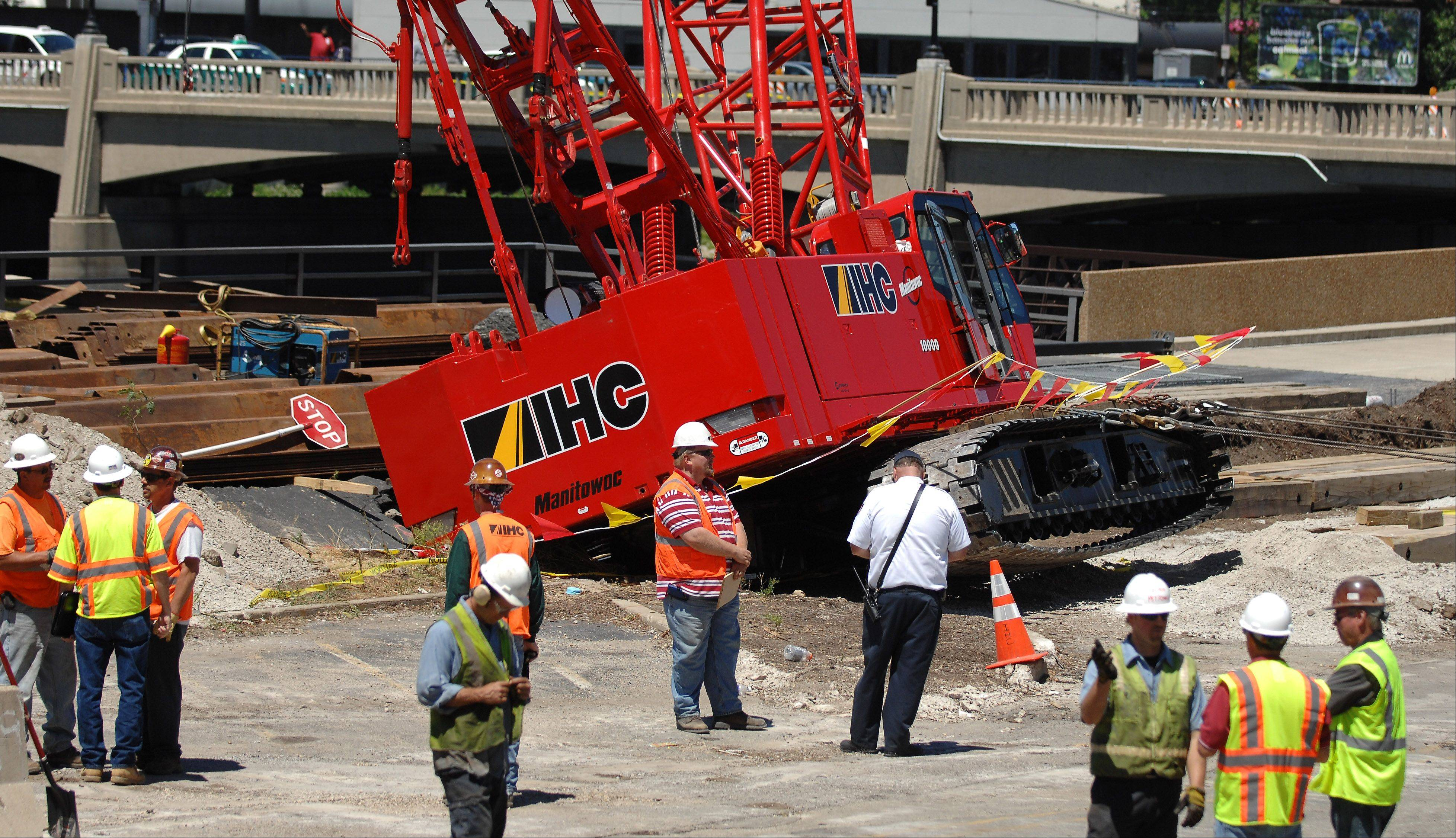 A construction crane fell through an unsupported portion of Riverside Drive Monday in downtown Elgin while working on the promenade project. Another crane was brought in to try to pull this one out of the hole.