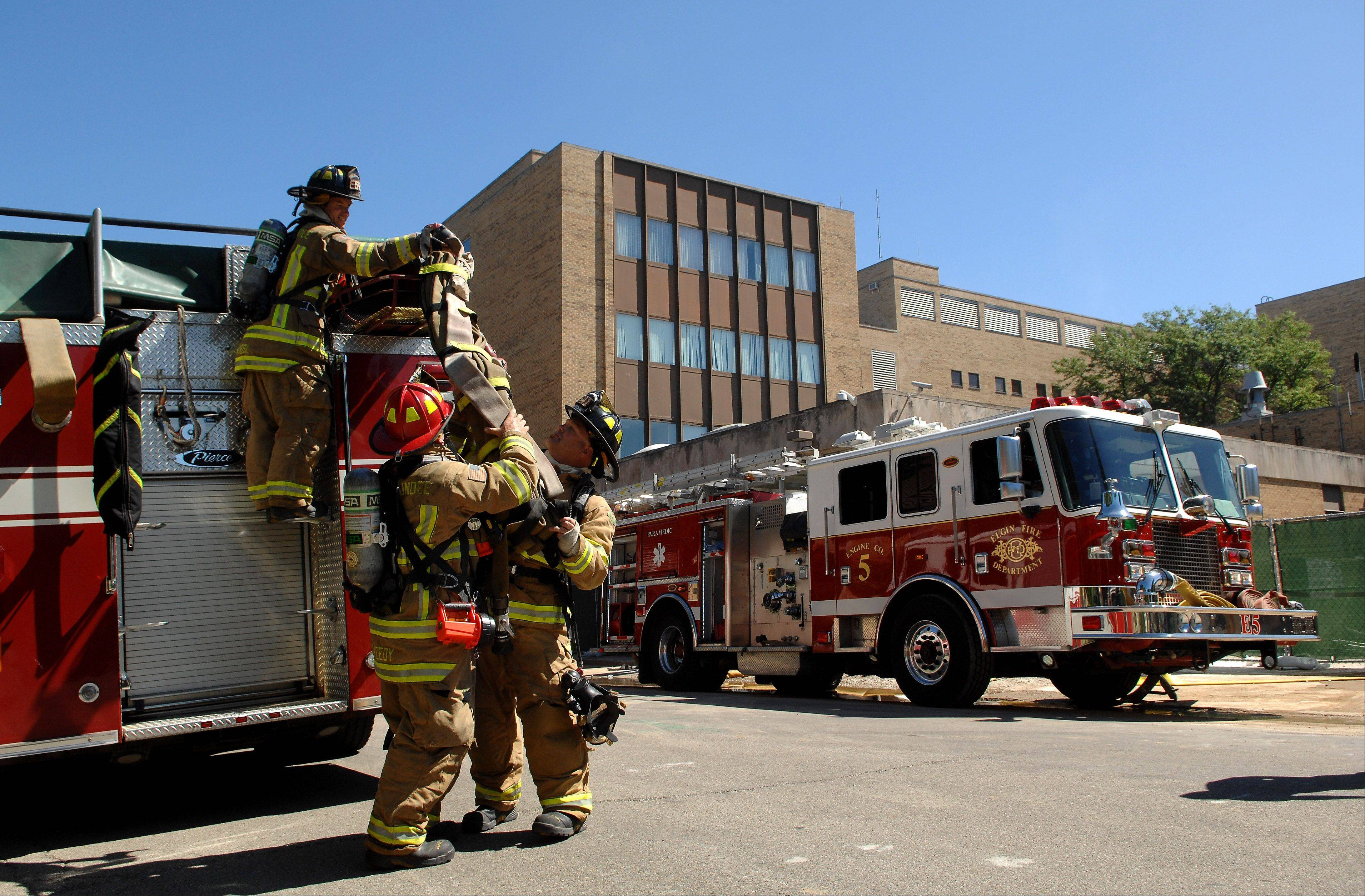 Rutland-Dundee firefighters unload a hose from their engine Monday at the old Sherman Hospital on Elgin's east side. More than 300 firefighters from the area are participating in high-rise training this week, conducted by the Elgin Fire Department. Training continues through Friday.