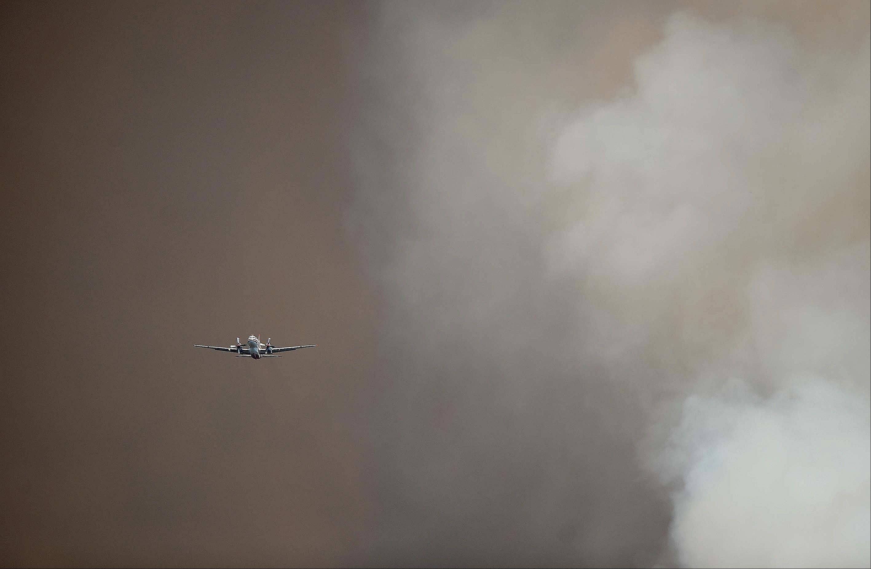 A slurry plane flies through smoke from a wildfire burning west of Manitou Springs, Colo., on Sunday, June 24, 2012. The fire erupted and grew out of control to more than 3 square miles early Sunday, prompting the evacuation of more than 11,000 residents and an unknown number of tourists.