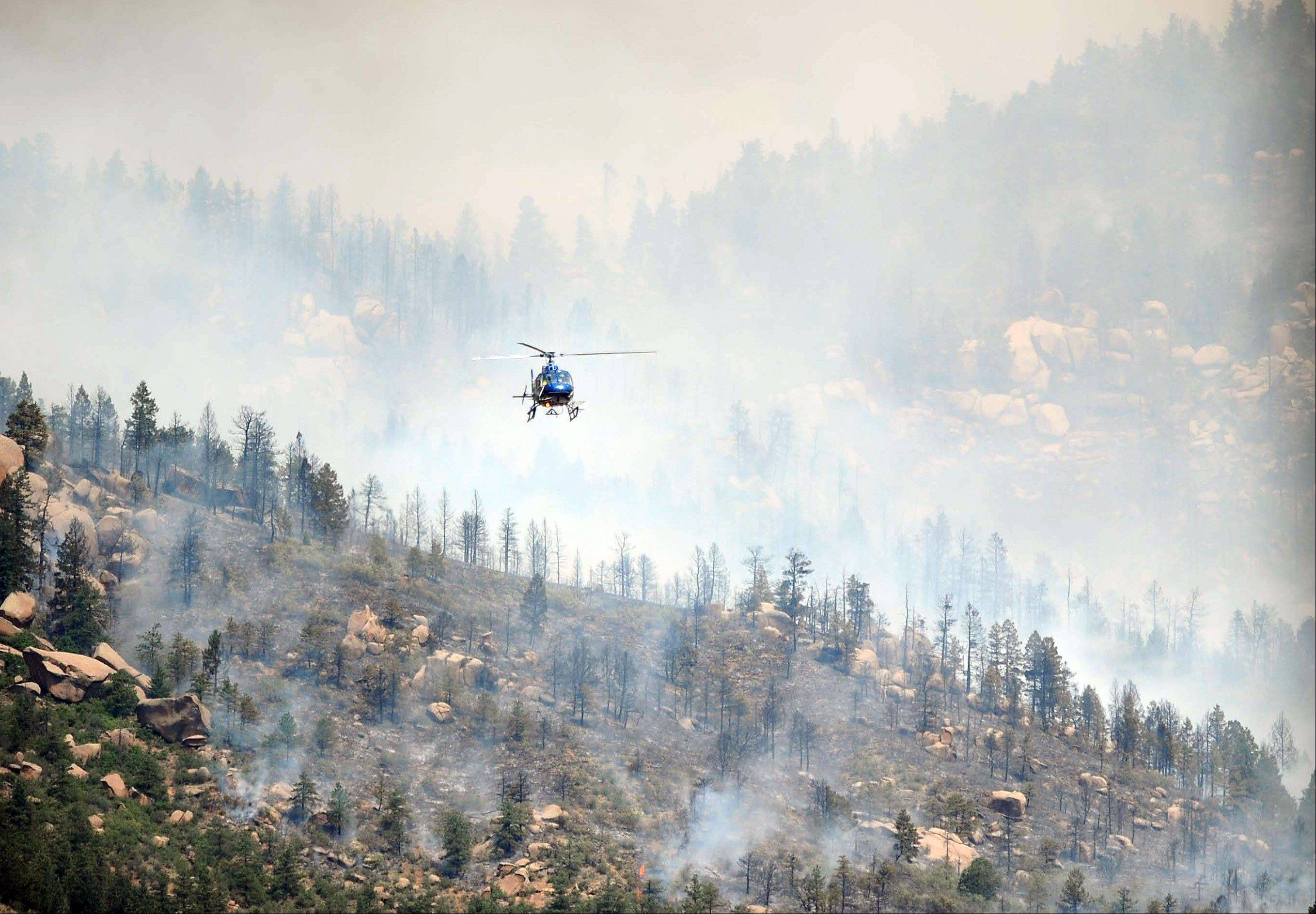 A helicopter flies over a wildfire burning west of Manitou Springs, Colo., on Sunday, June 24, 2012. The fire erupted and grew out of control to more than 3 square miles early Sunday, prompting the evacuation of more than 11,000 residents and an unknown number of tourists.