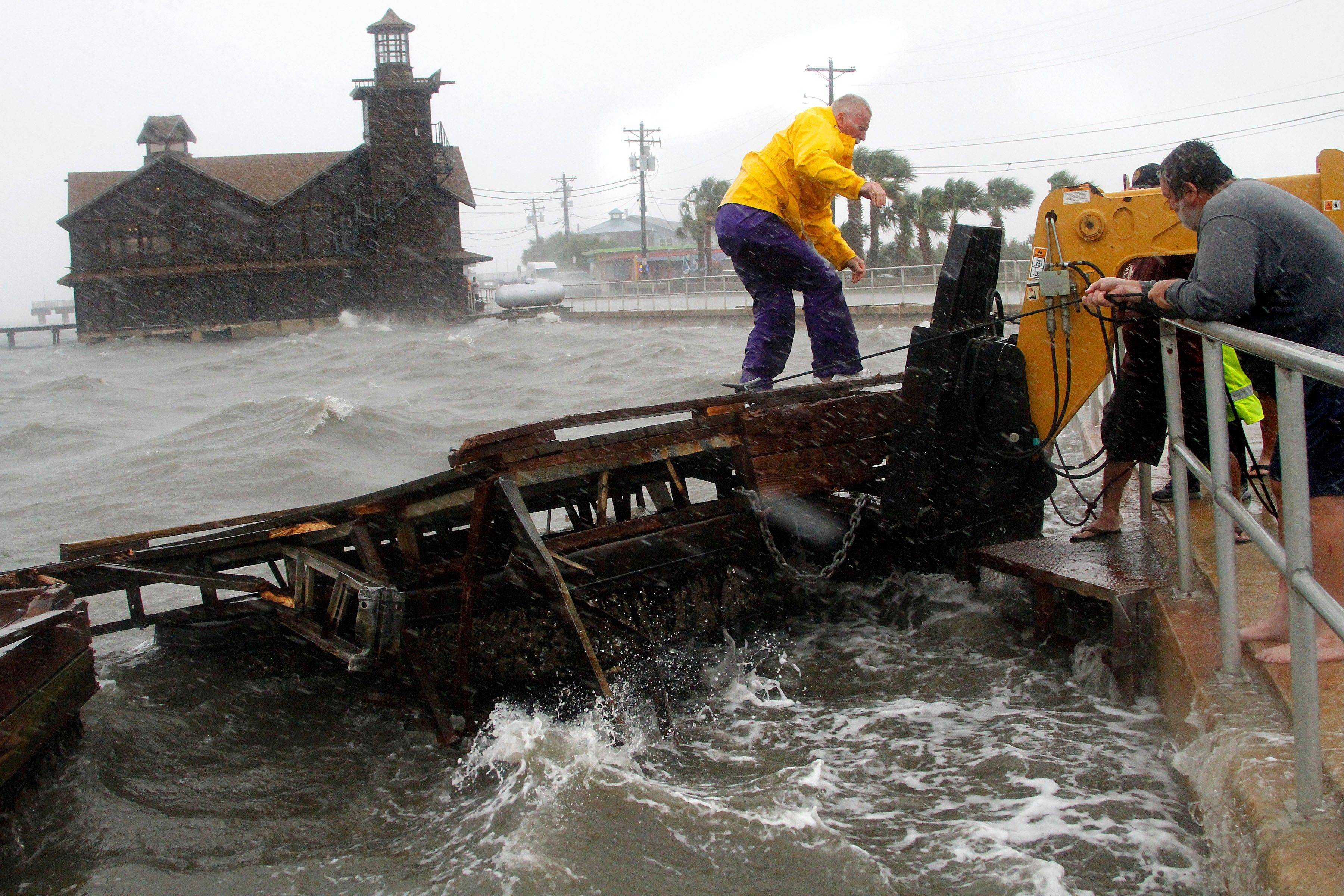 Cedar Key Fire Chief Robert Robinson walks on a section of a floating dock that broke loose during a storm surge from Tropical Storm Debby in Cedar Key, Fla., on Sunday, June 24, 2012. Slow-moving Tropical Storm Debby's outer bands lashed Florida with rain and kicked up rough surf off Alabama on Sunday, prompting storm warnings for those states.
