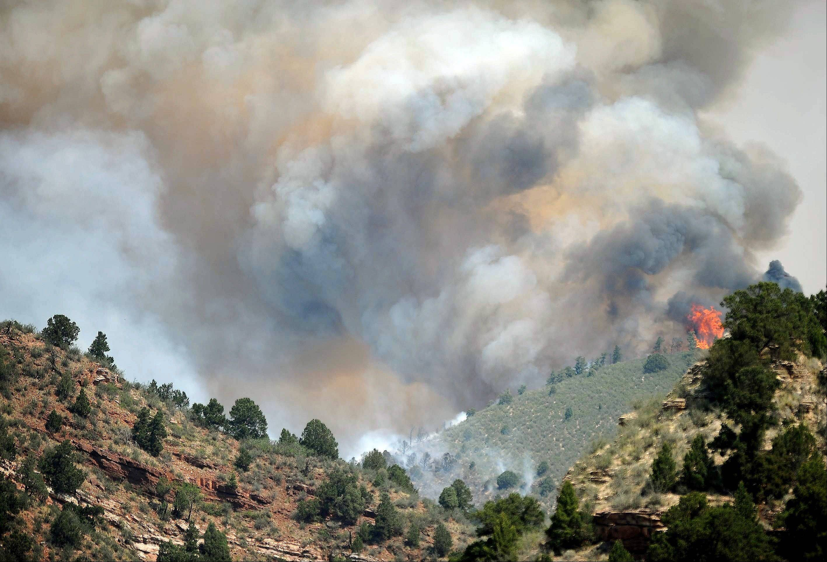 A wildfire burns west of Manitou Springs, Colo., on Sunday, June 24, 2012. The fire erupted and grew out of control to more than 3 square miles early Sunday, prompting the evacuation of more than 11,000 residents and an unknown number of tourists.
