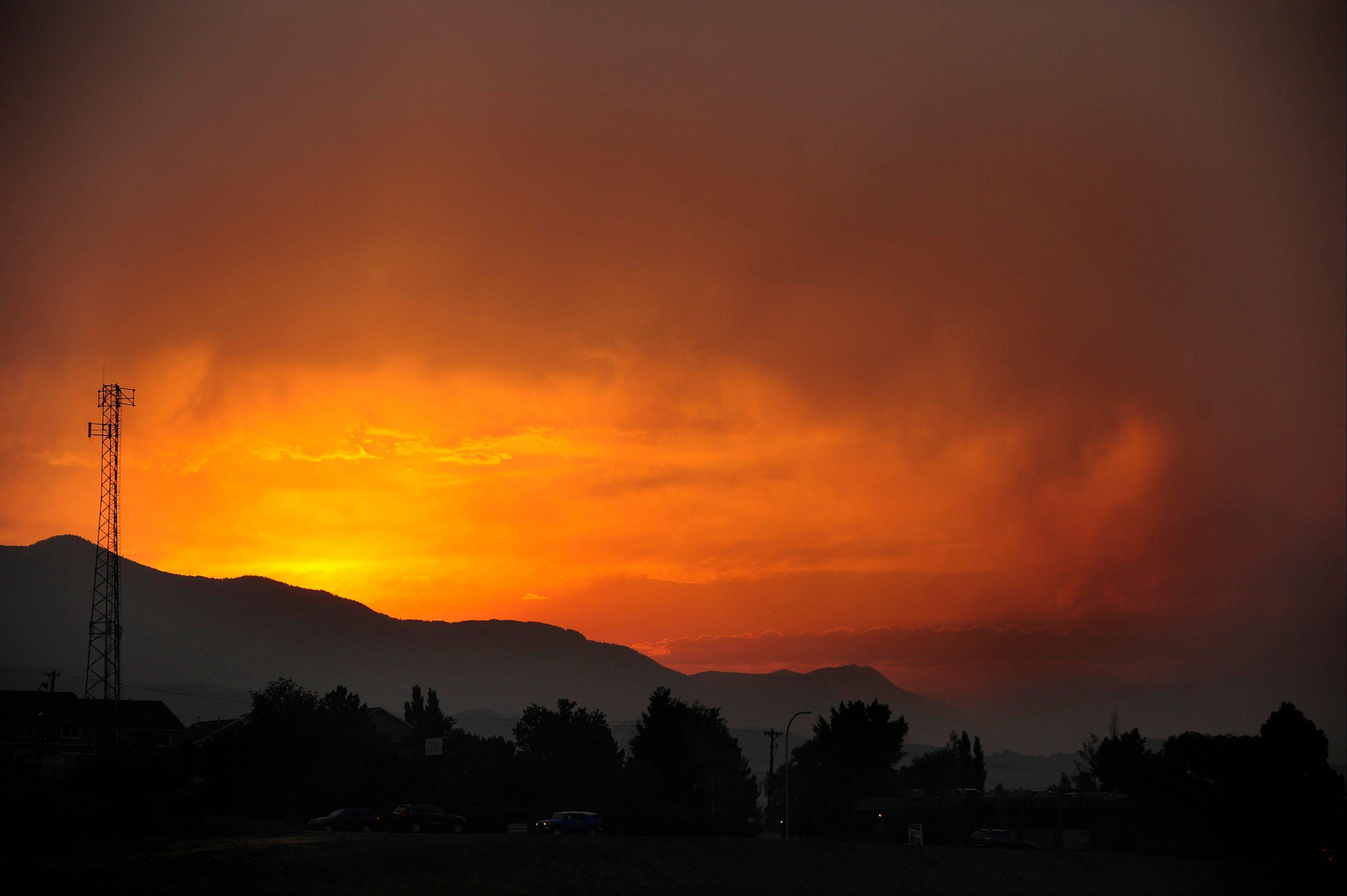 The sun sets as seen from Lower Gold Camp Road as a wildfire continues to burn west of Colorado Springs, Colo. on Sunday, June 24, 2012. The fire erupted Saturday and grew out of control to more than 3 square miles early Sunday, prompting the evacuation of more than 11,000 residents and an unknown number of tourists.