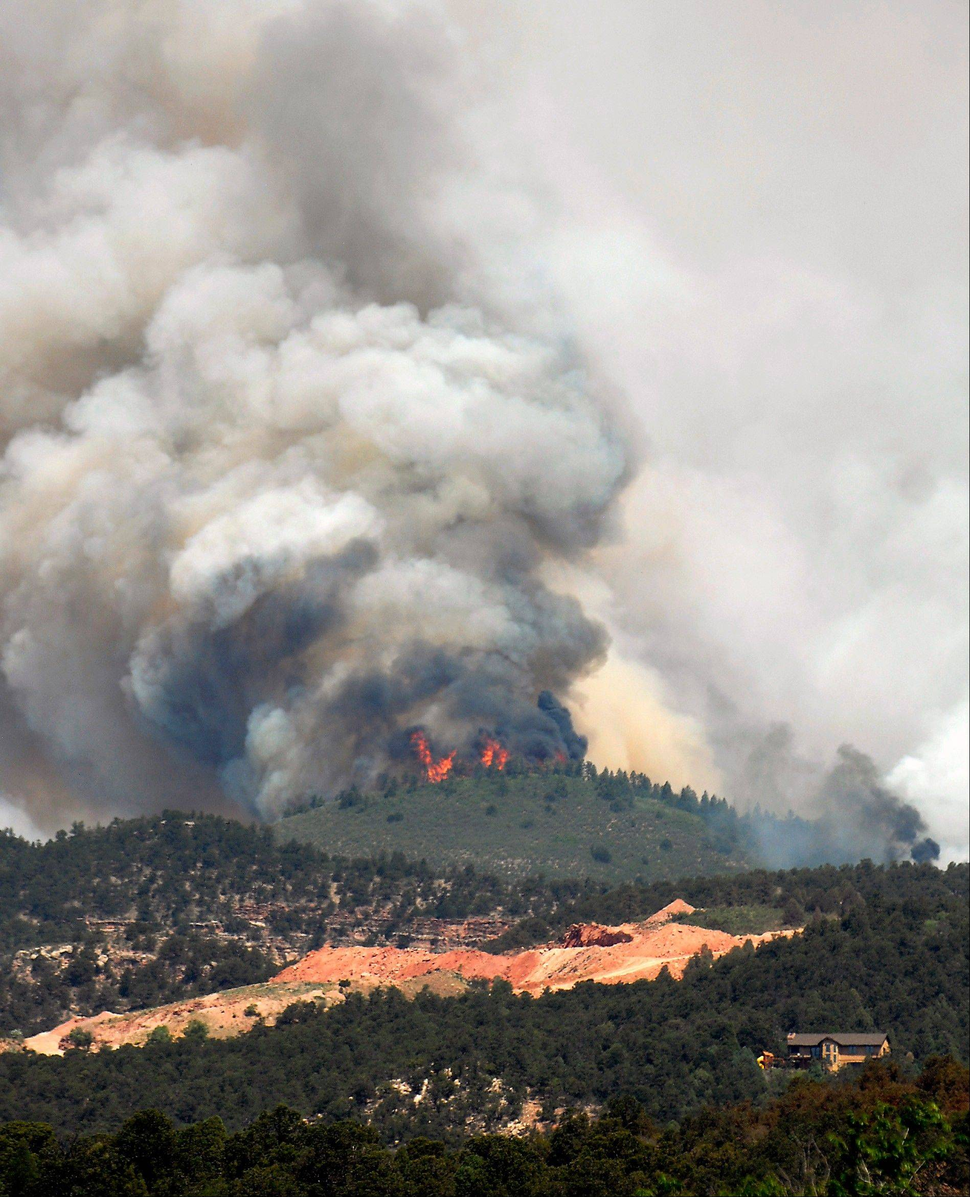Smoke billows from a wildfire burning near Colorado Springs, Colo., on Sunday, June 24, 2012. The fire erupted and grew out of control to more than 3 square miles early Sunday, prompting the evacuation of more than 11,000 residents and an unknown number of tourists. On Saturday, a blaze destroyed 21 structures near the mountain community of Estes Park.
