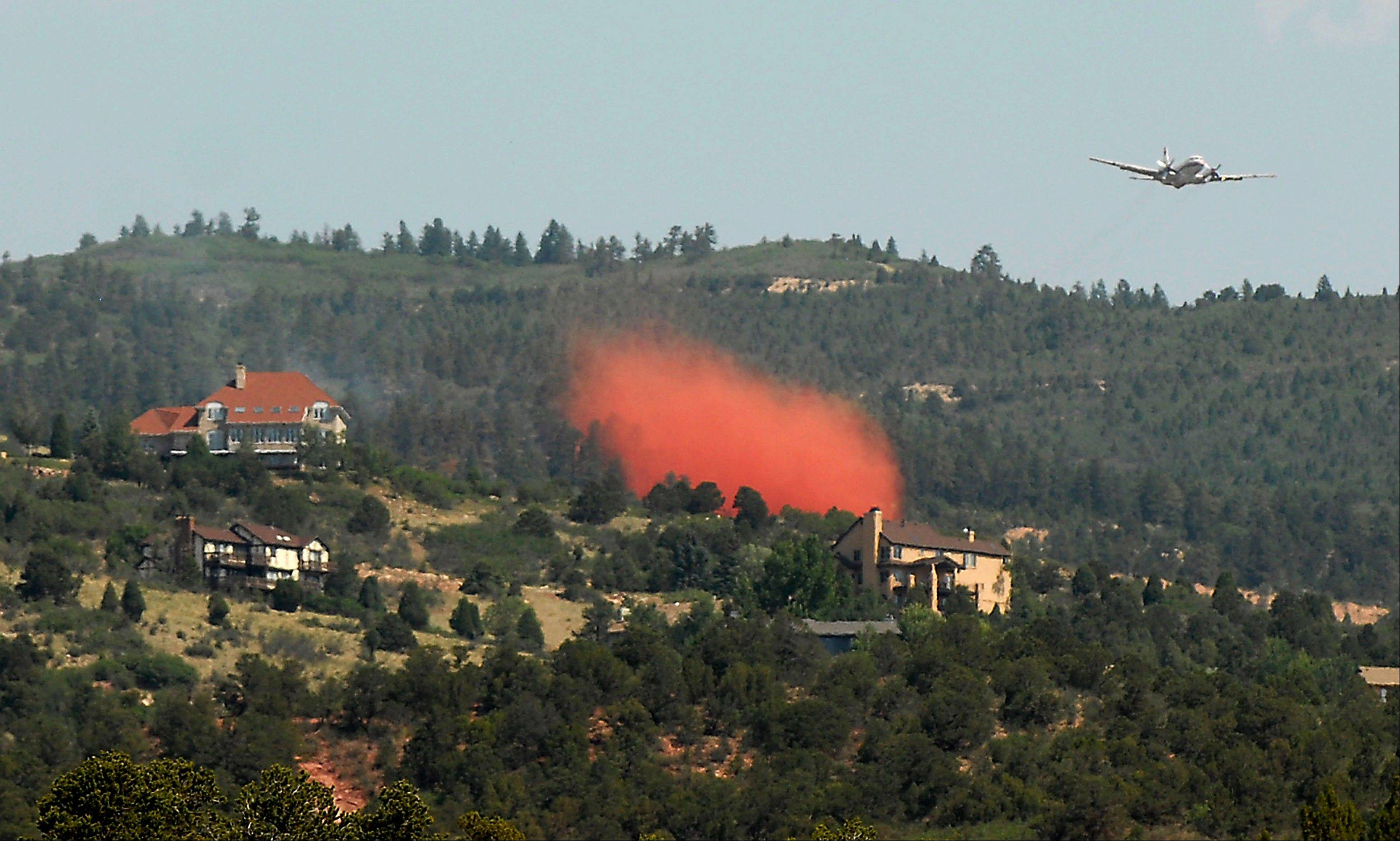 A helicopter drops water on a wildfire near Colorado Springs, Colo., on Sunday, June 24, 2012. The fire erupted and grew out of control to more than 3 square miles early Sunday, prompting the evacuation of more than 11,000 residents and an unknown number of tourists. On Saturday, a blaze destroyed 21 structures near the mountain community of Estes Park.