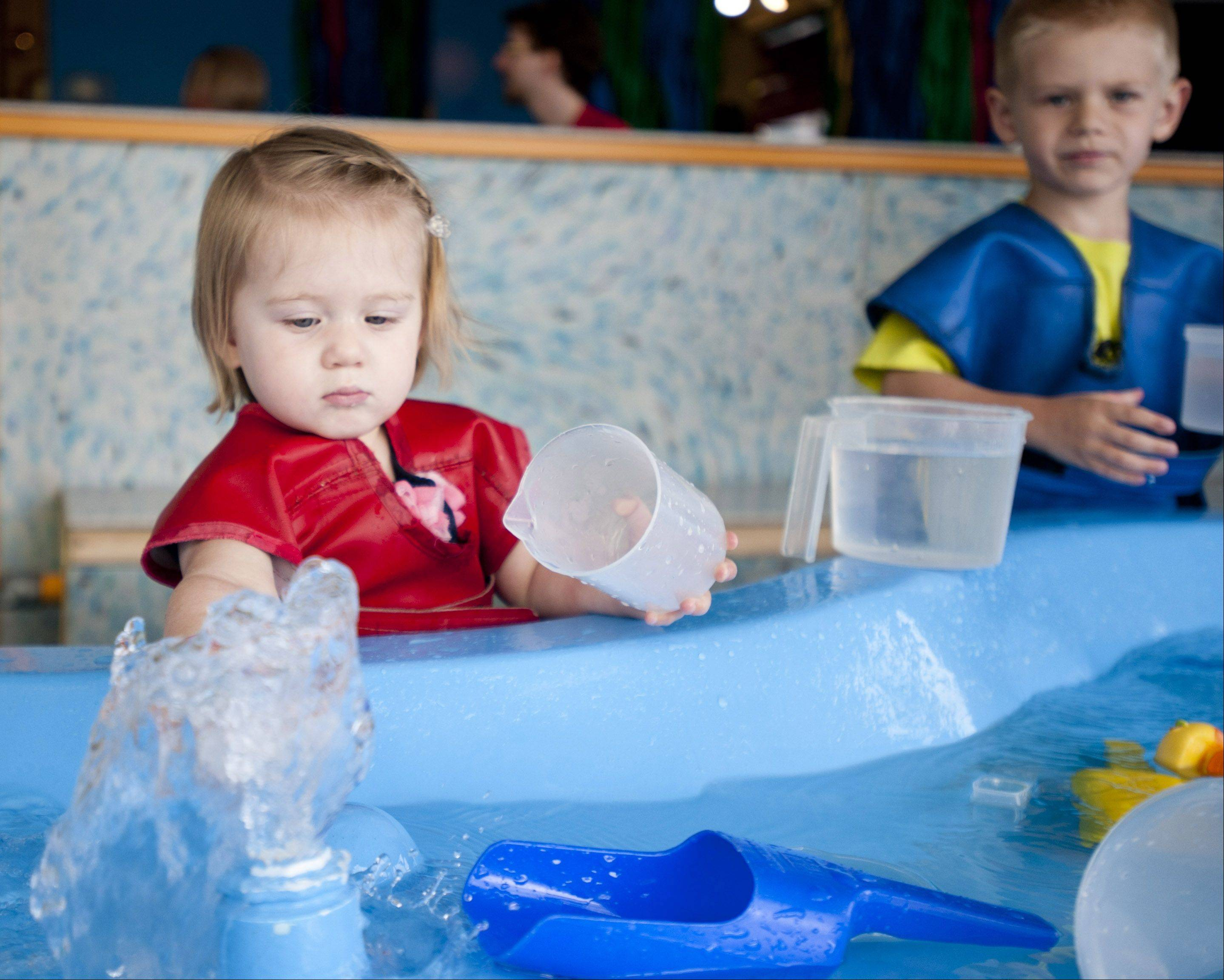 Keeley Sparks, 1, enjoys the WaterWays exhibit during the DuPage Children's Museum's 25th anniversary celebration on Sunday. The event featured an insect zoo, train rides and art activities.