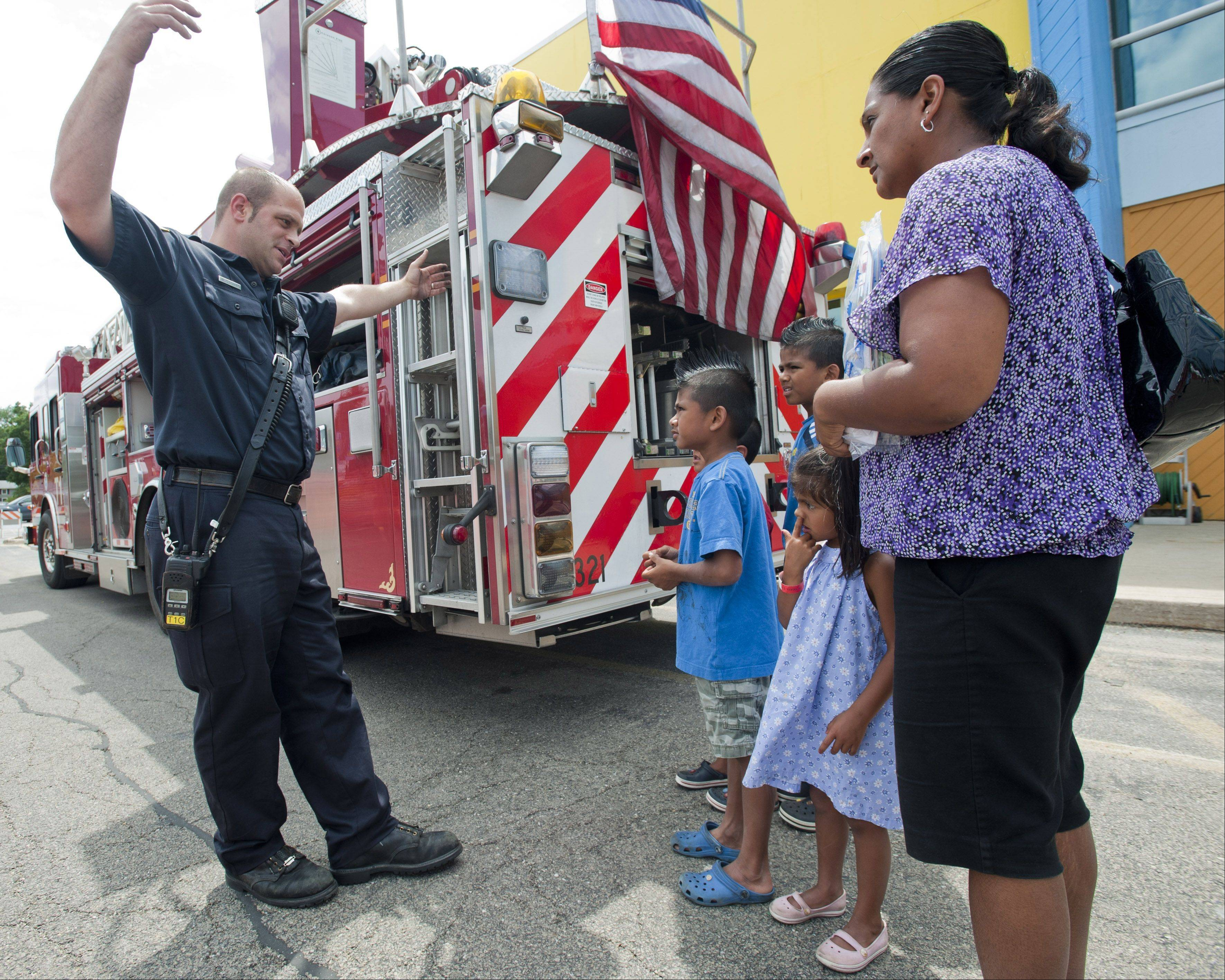 Firefighter Jim Perkovich explains fire truck instruments to visitors of the DuPage Children's Museum's 25th anniversary celebration. Those who attended enjoyed train rides, art activities, music and the ever popular Touch-a-Truck outside the museum.