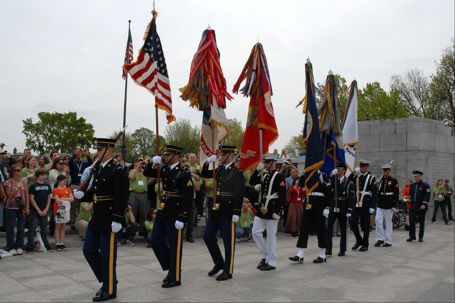 The Honor Flight Chicago trip includes a visit to the World War II Memorial in Washington, D.C., where veterans and visitors see a color guard ceremony.