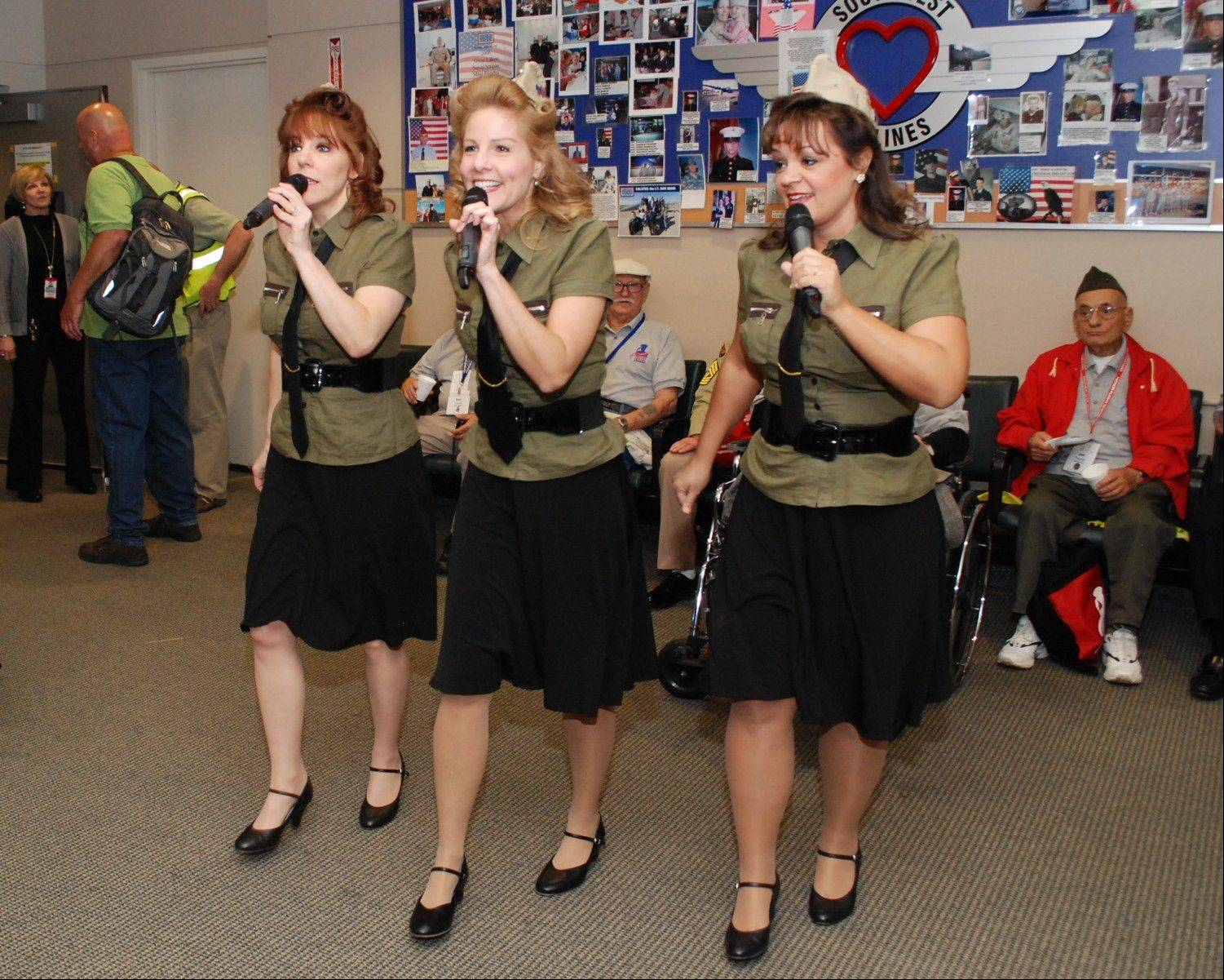 The Legacy Girls perform Andrews Sisters-style to entertain the veterans before the flight leaves from Midway Airport.
