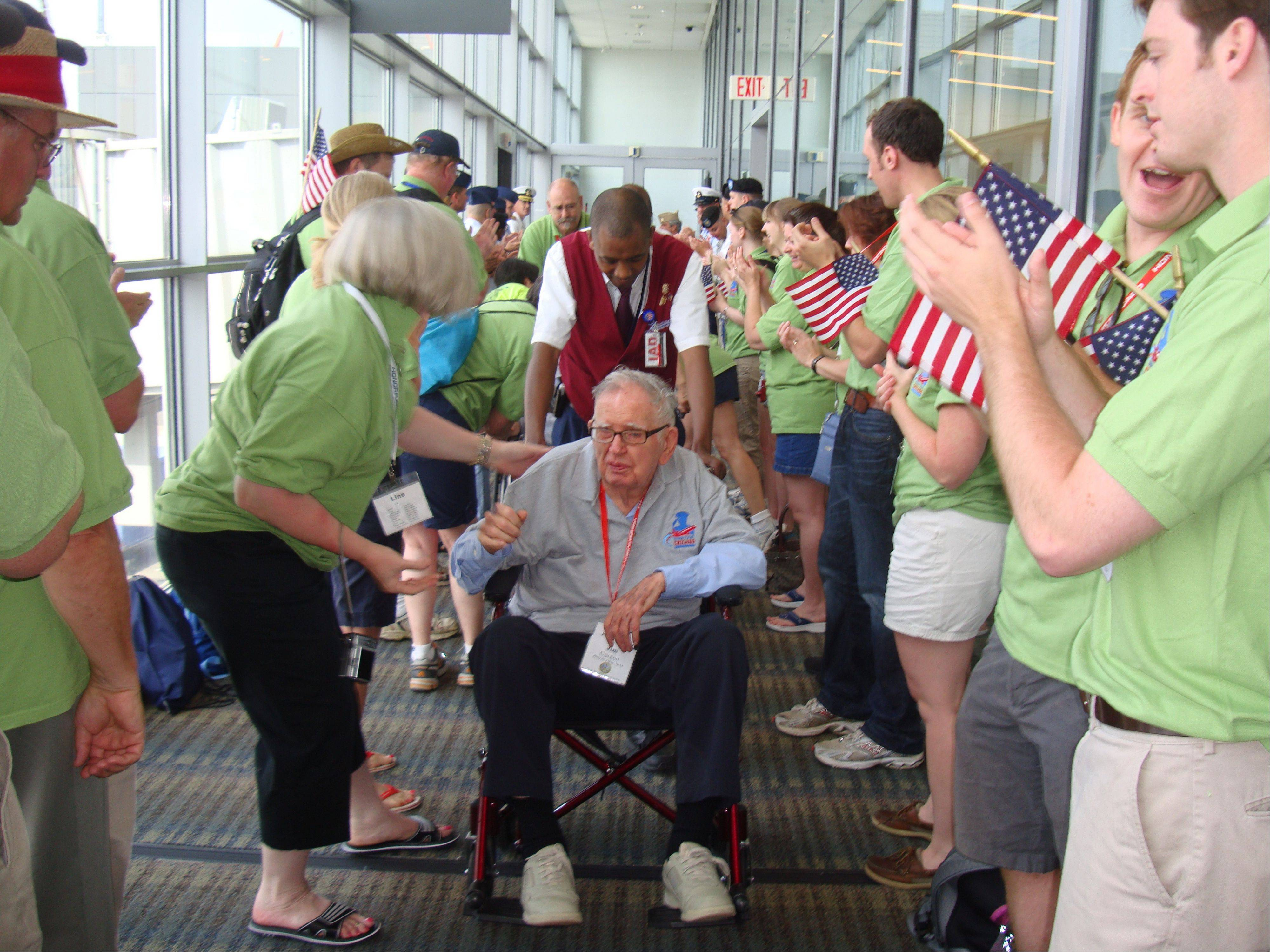 Volunteers cheer and wave flags for veterans like James Carson as they arrive at airports on both ends of the Honor Flight Chicago trips to Washington, D.C.