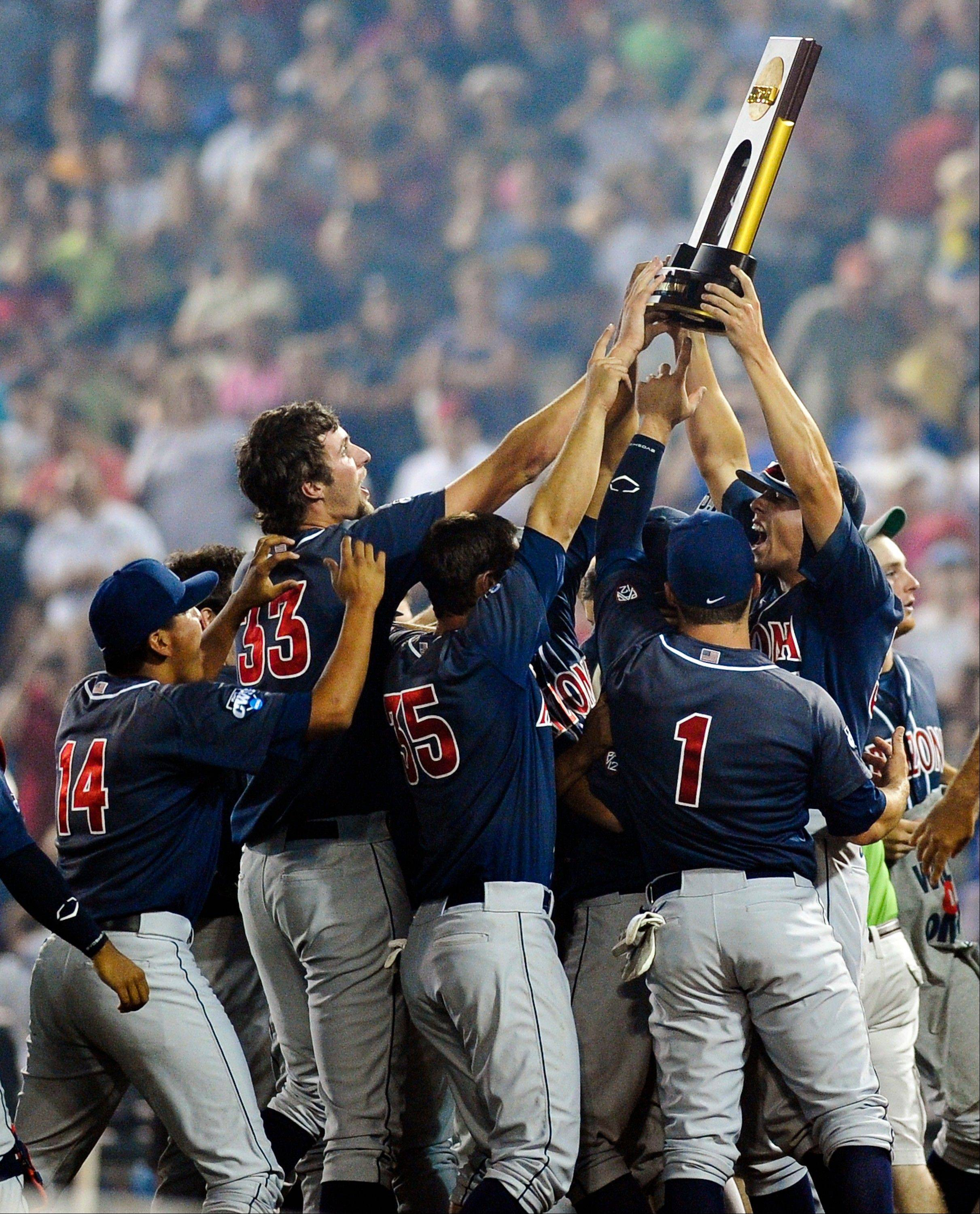 Arizona players hoist the trophy Monday after defeating South Carolina 4-1 in Game 2 to win the NCAA College World Series baseball finals in Omaha, Neb.