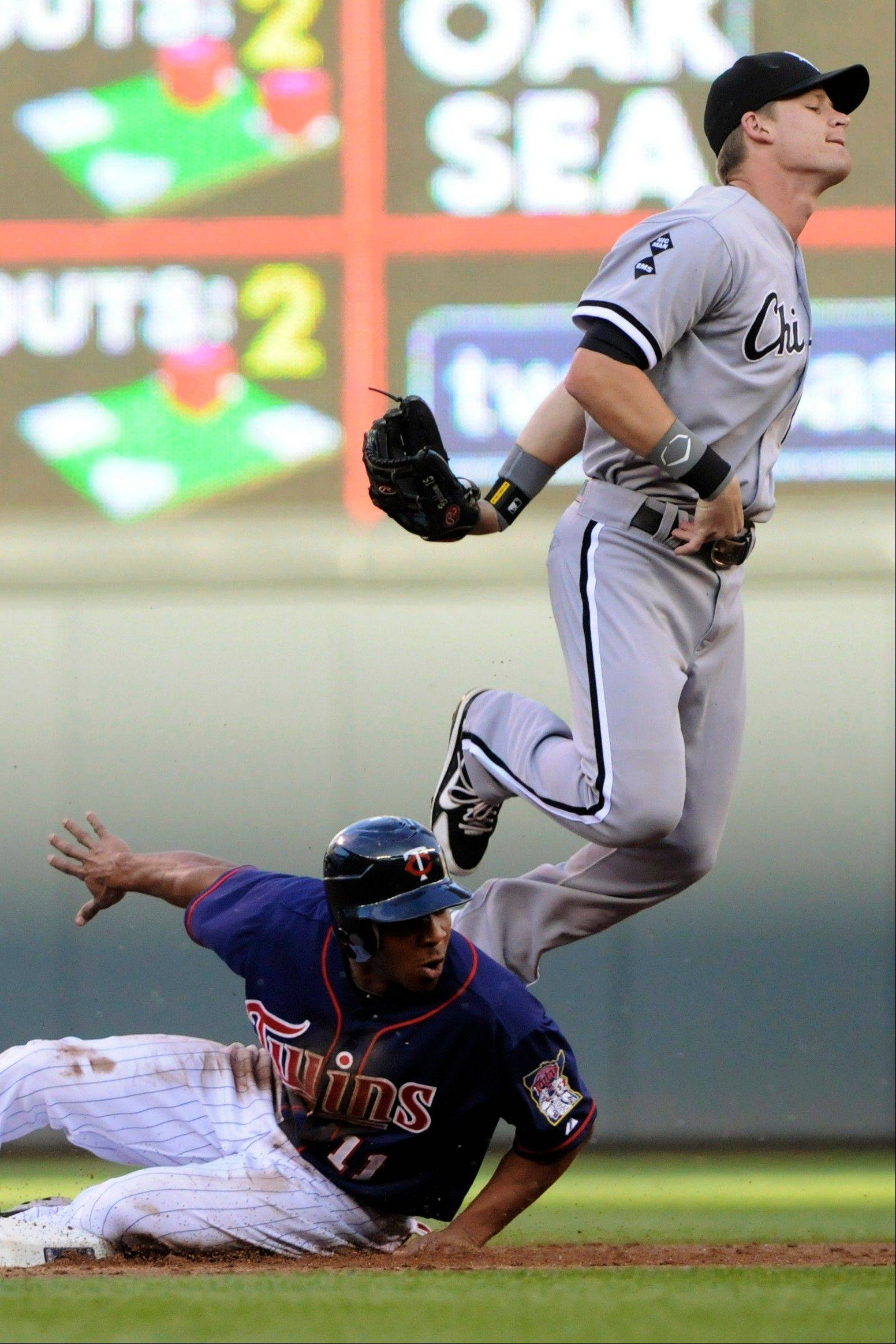 Minnesota Twins' Ben Revere, left, looks back after the force at second as Chicago White Sox second baseman Gordon Beckham completes the double play hit into by Josh Willingham in the first inning of a baseball game, Monday in Minneapolis.