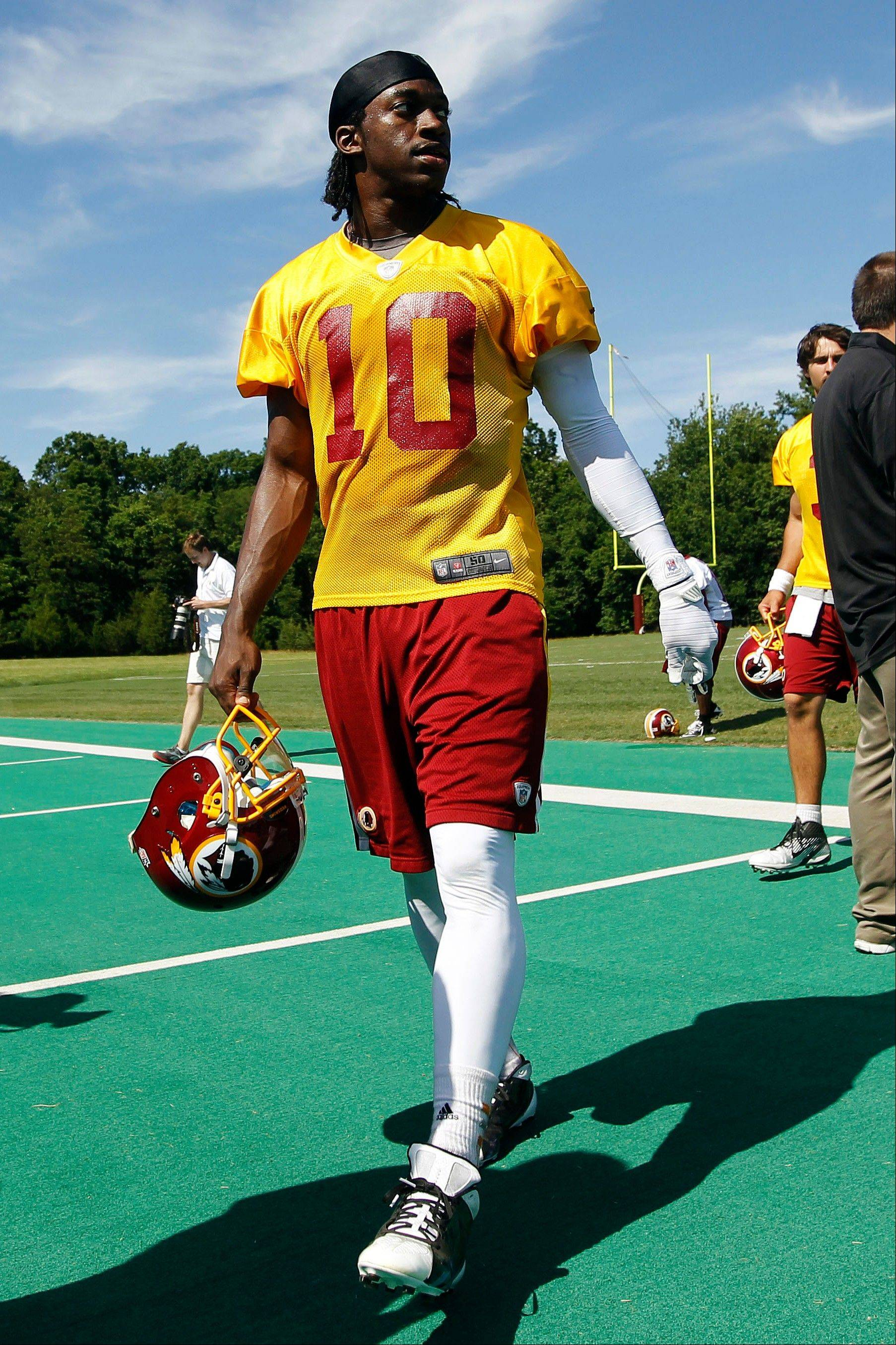 In this June 13, 2012, file photo, Washington Redskins quarterback Robert Griffin III walks off the field following NFL football practice in Ashburn, Va. Former Baylor basketball player Richard Khamir Hurd is facing federal extortion charges in the case. Hurd made his first appearance Monday in federal court in Waco, Texas.