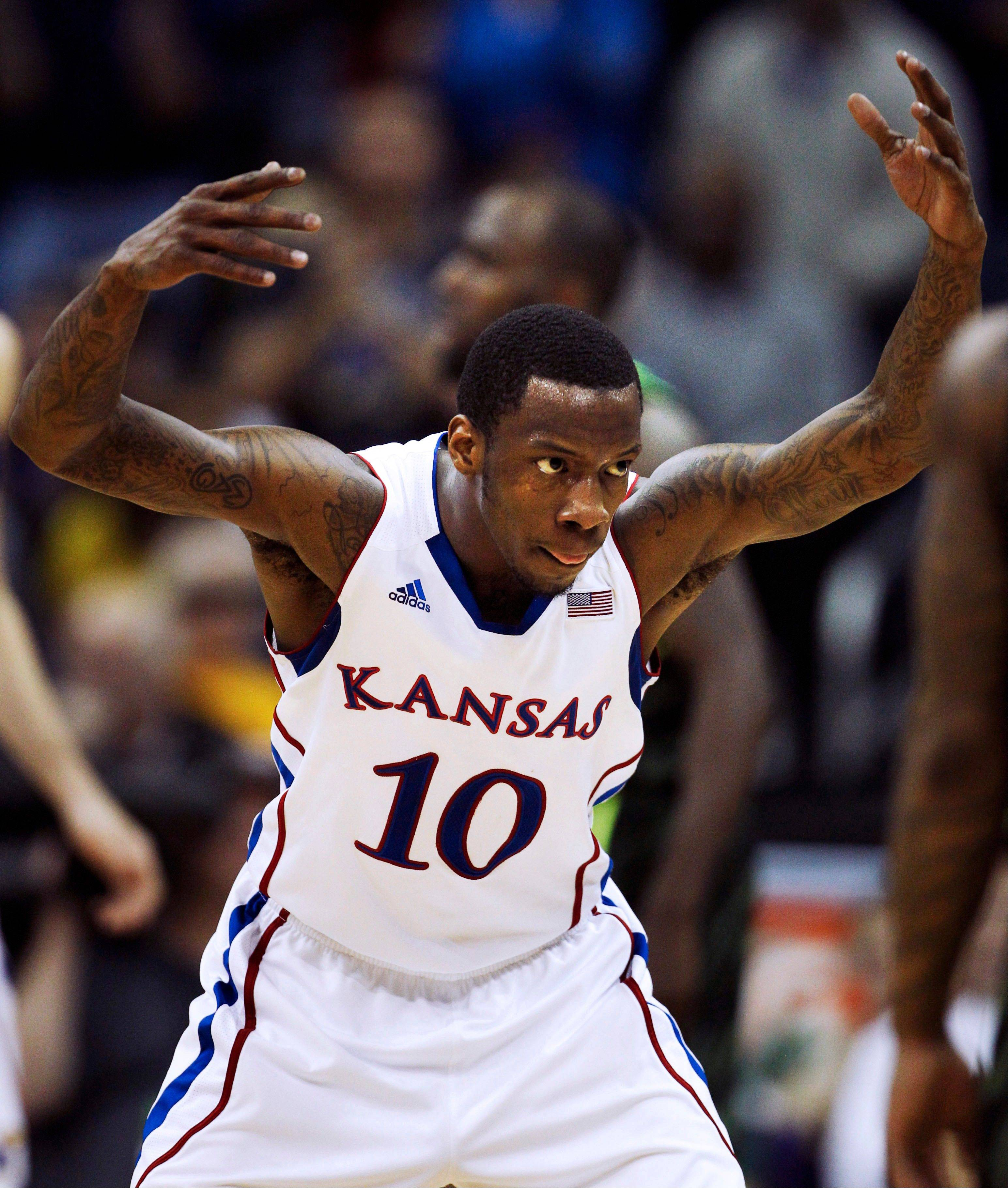 Kansas guard Tyshawn Taylor (10) signals to the crowd during the second half of an NCAA college basketball game against Baylor in the Big 12 Conference tournament Friday, March 9, 2012, in Kansas City, Mo. Taylor scored 20 points in the game.