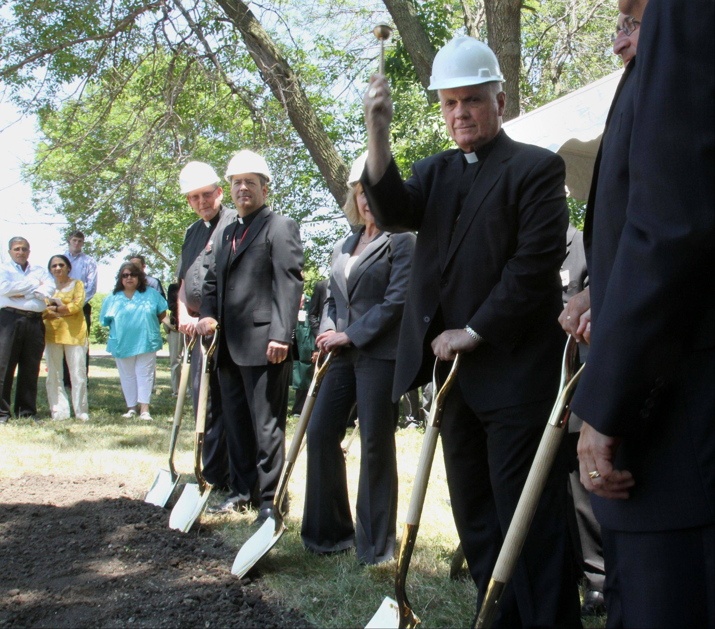 The Most Rev. George Rassas, auxiliary bishop of Chicago, places holy water on the ground at Alexian Brothers Health System's groundbreaking for a $7.5 million free-standing hospice residence in Elk Grove Village on Tuesday.