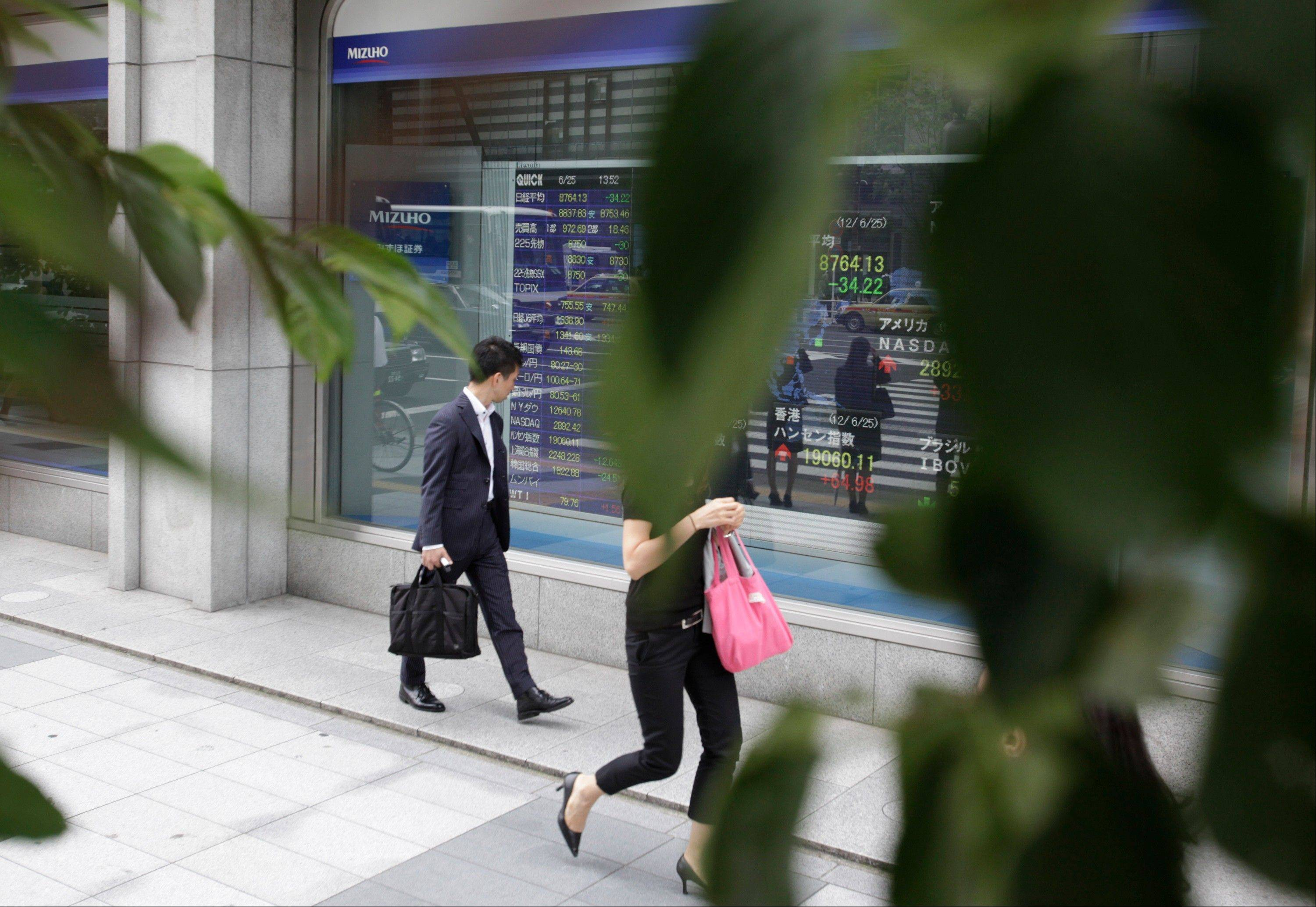 Associated PressA businessman checks a securities firm's electronic stock board in Tokyo Monday.
