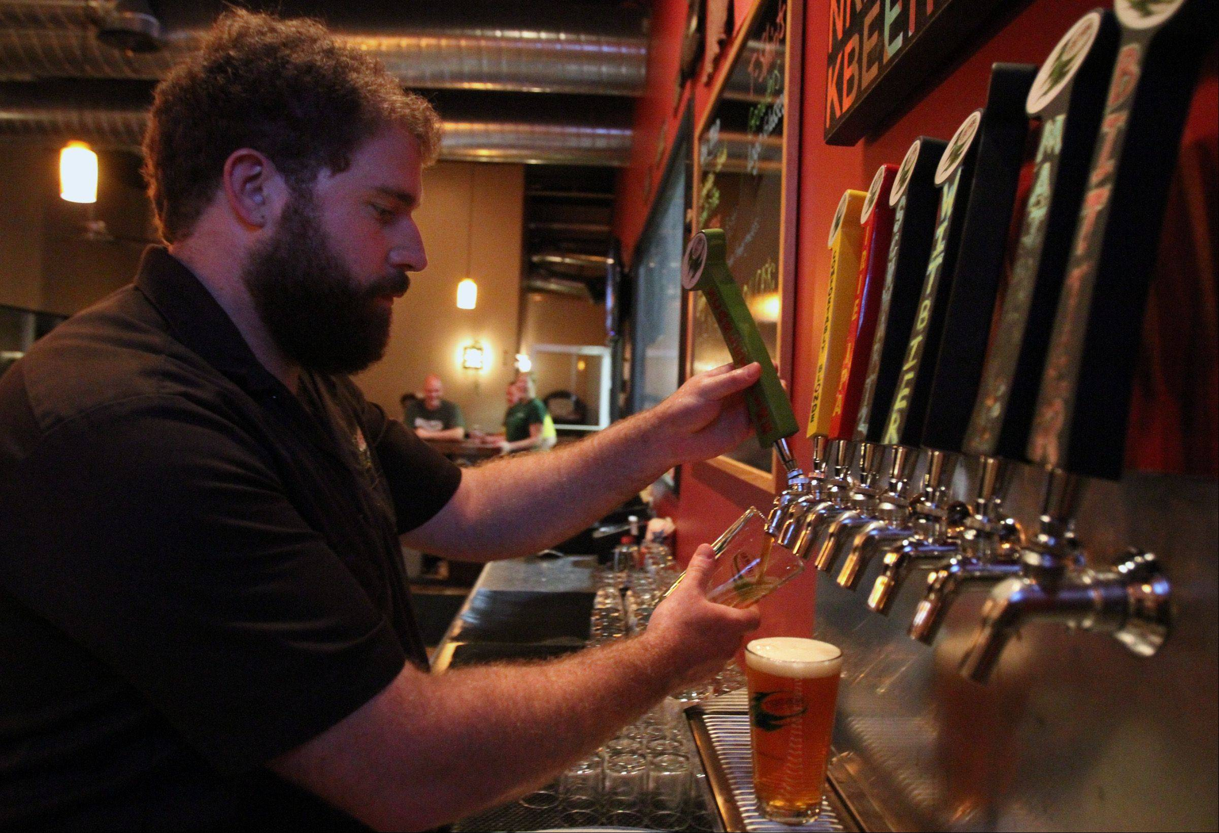 Tighthead Brewing Company tap room manager Patrick Whisler draws a beer at the brewery in Mundelein.