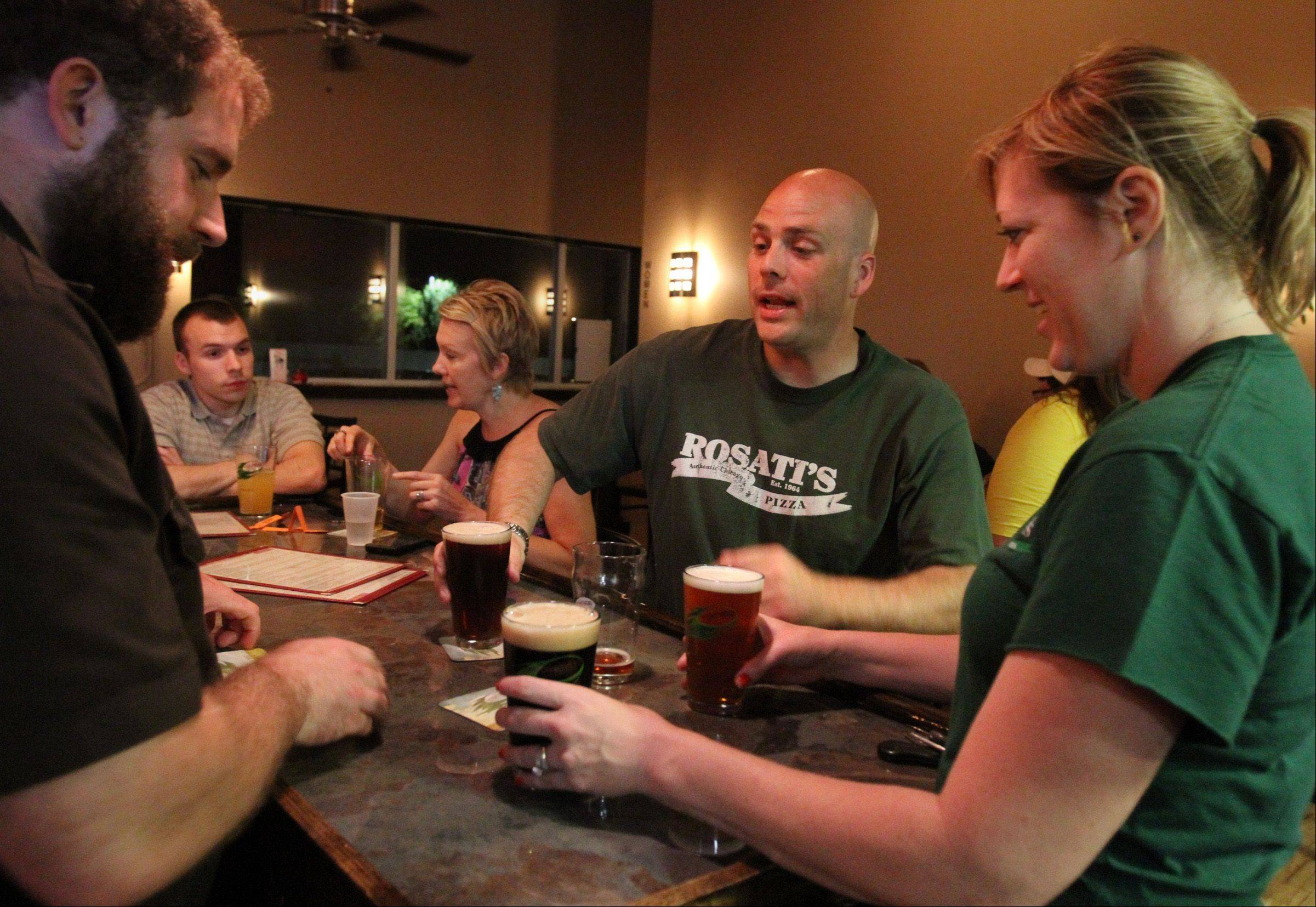 Tighthead Brewing Company tap room manager Patrick Whisler, left, serves Pat O'Connell and Abby Hickman, both of Libertyville.