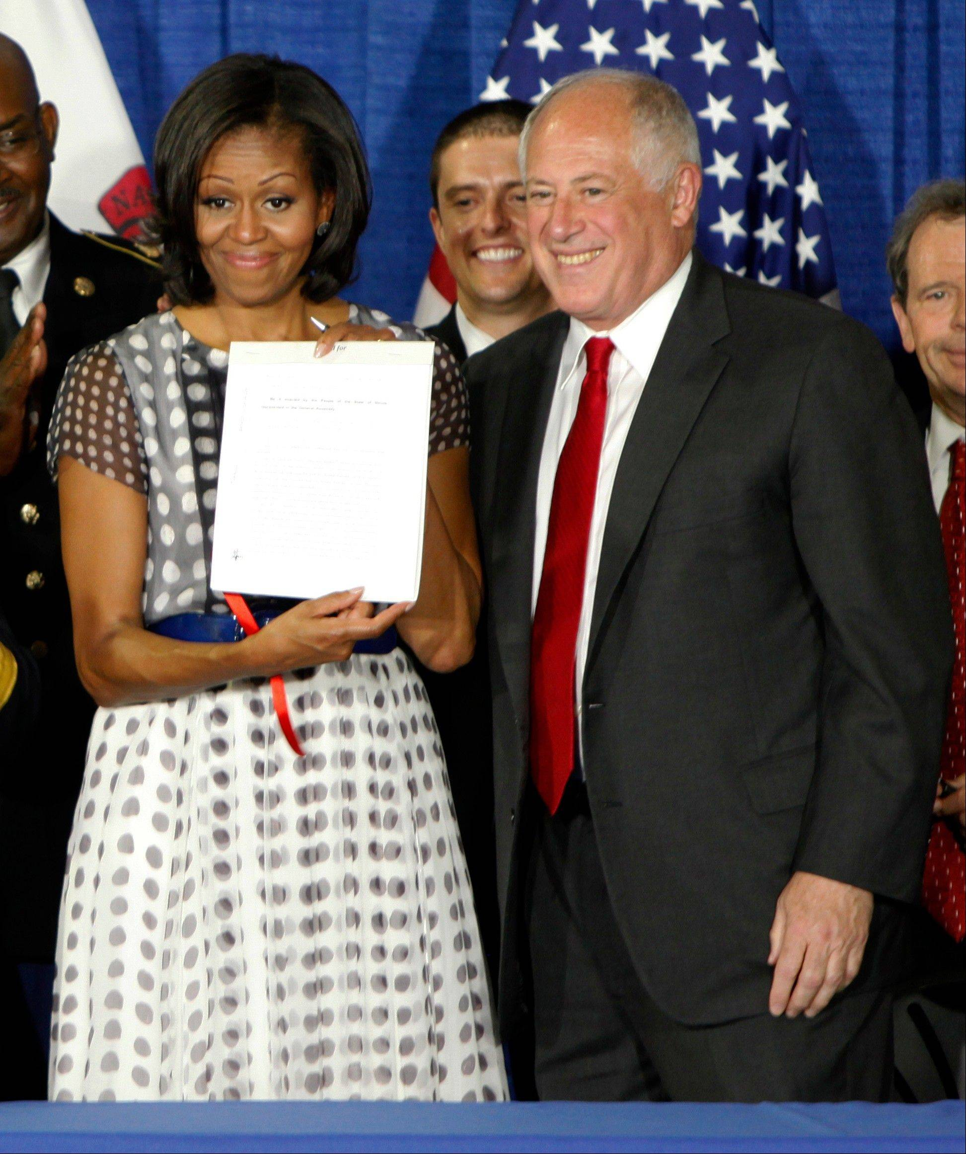 first lady Michelle Obama stands with Gov. Pat Quinn after Illinois becomes the 23rd state to enact a law allowing military personnel and their spouses a quicker transfer of their professional licenses to Illinois during a military relocation.