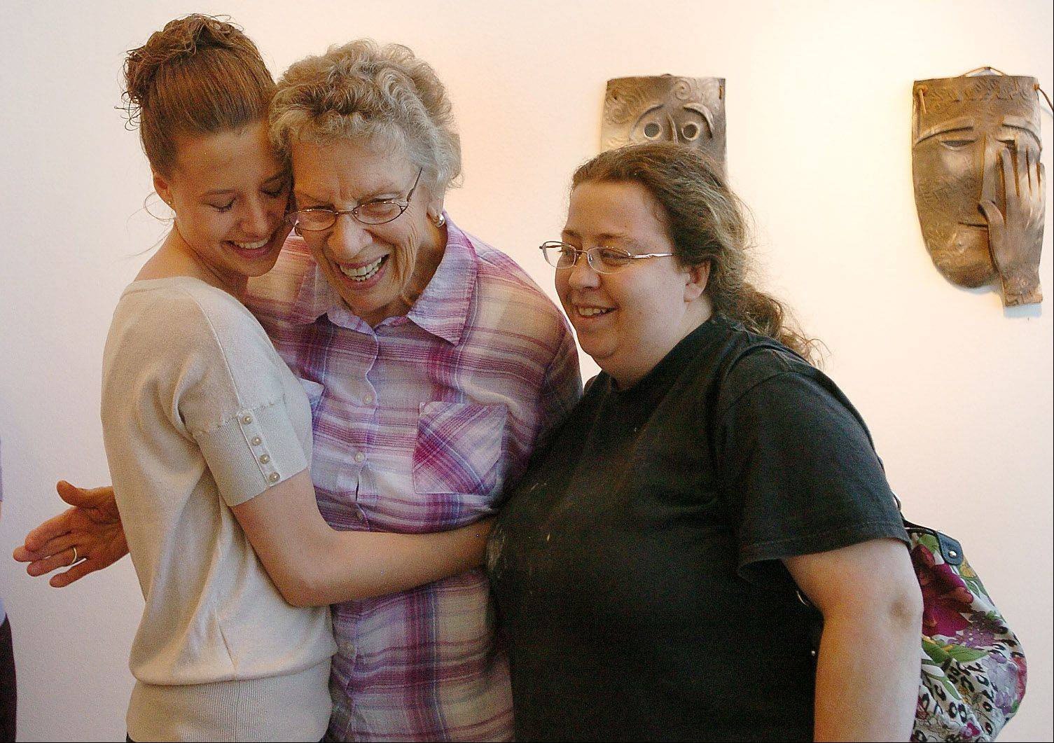 Mary Applegate gets a hug from former art student colleagues, Christine Rueger, left, and Jill Popp, at Mary's sculpture exhibition reception. The 89-year-old Palatine artist's work is on display at the college through July 18.