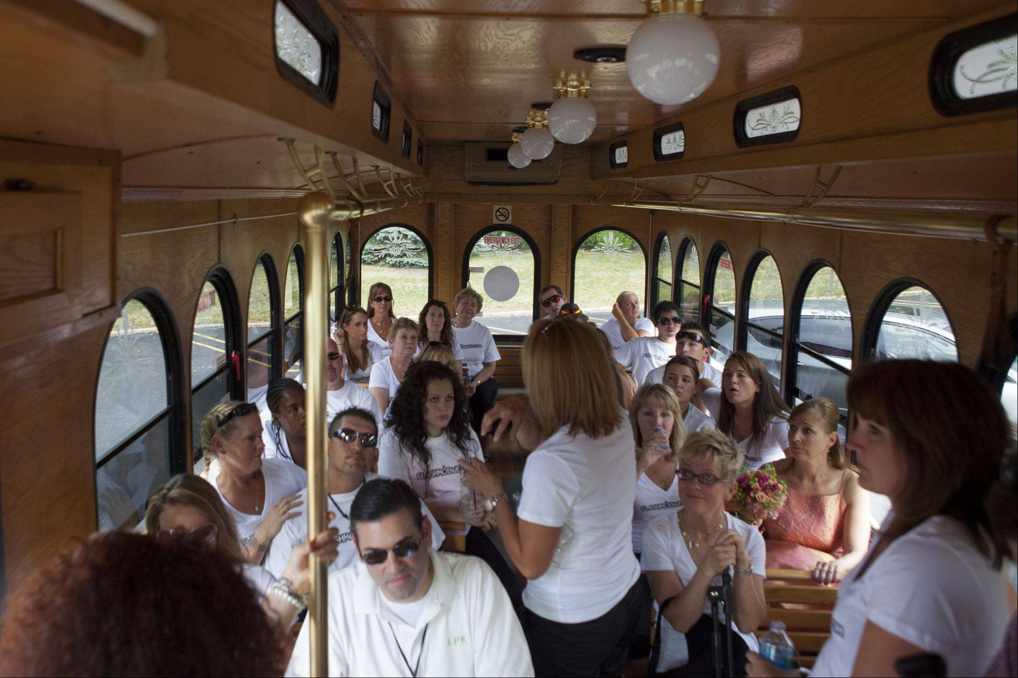 A group of 25 gather inside a trolley as they prepare to go to the home of Libby Watkins and Mike Conjura to set up a wedding that only the couple knew about.