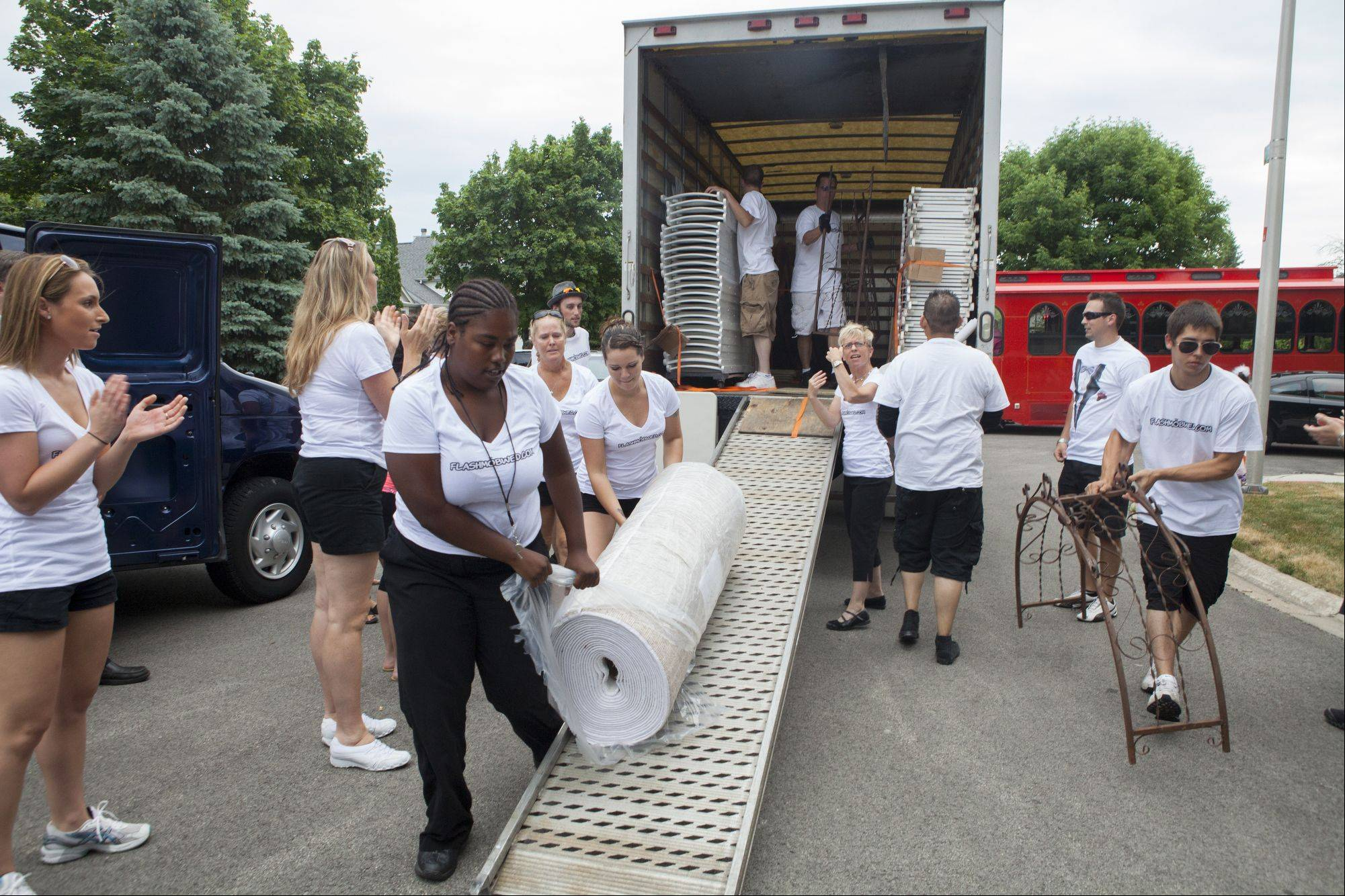 "Members of the flash mob wed team pull the runner for the ceremony out of a truck that was ""late"" carrying tables and chairs for Libby Watkins and Mike Conjura's retirement party. They surprised their family and friends on Sunday when they decided to get married at their home in Schaumburg."