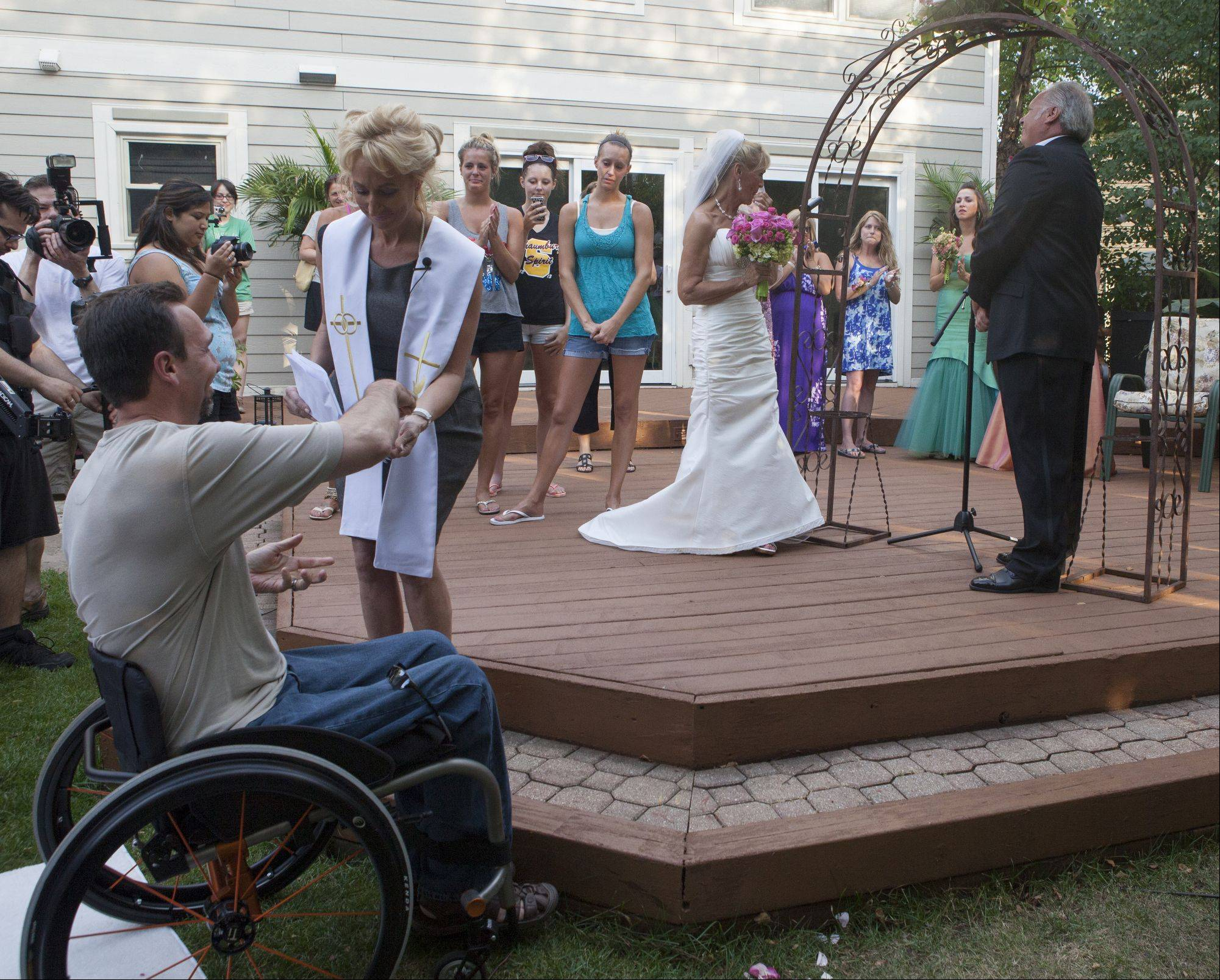 John Schomer, a friend of Libby Watkins and Mike Conjura, gives the wedding rings to Kim Panzarella who helped set up the event.