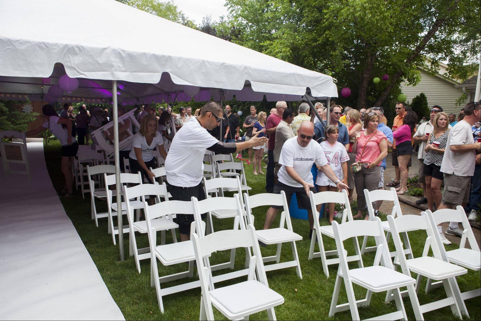 Mario Reyes directs the flash mob wedding team members as they quickly set up chairs for Libby Watkins and Mike Conjura's flash mob wedding.