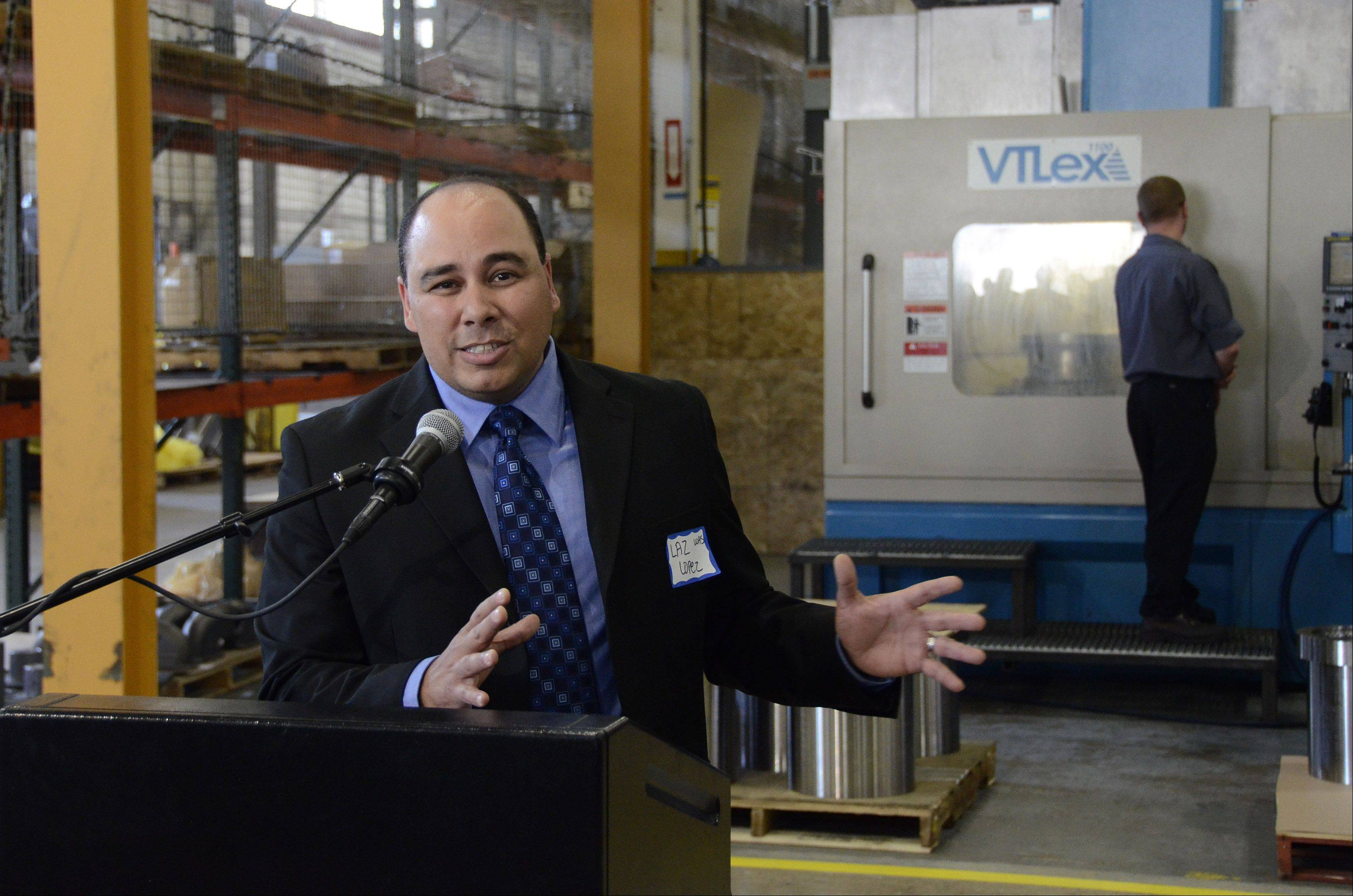 Wheeling High School Principal Laz Lopez speaks Wednesday at a news conference formally announcing the partnership between Harper College and more than 50 manufacturers for a new Advanced Manufacturing program. Behind him, an Acme Industries employee in Elk Grove Village works on a machine.