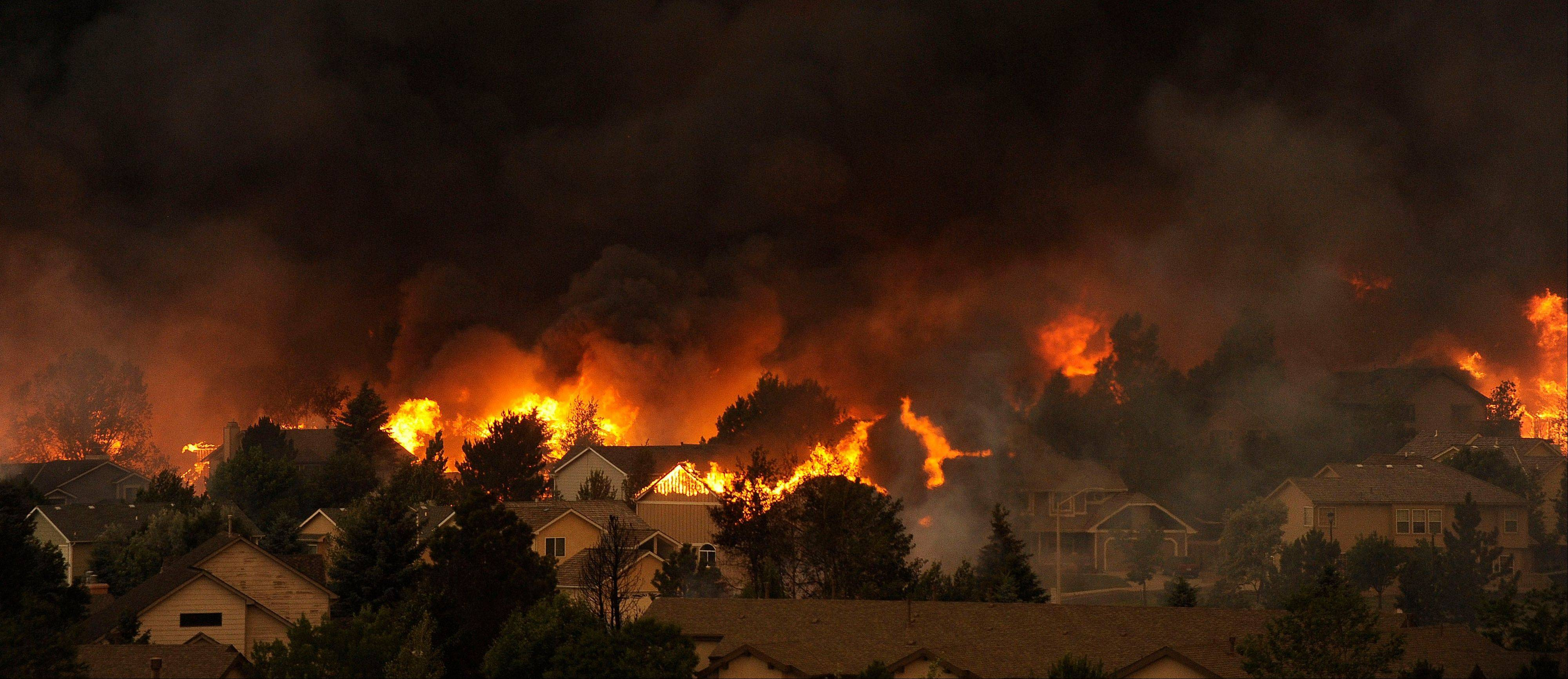 The Waldo Canyon fire burns an entire neighborhood in near the foothills of Colorado Springs, Colo. Tuesday, June 26, 2012. Colorado has endured nearly a week of 100-plus-degree days and low humidity, sapping moisture from timber and grass, creating a devastating formula for volatile wildfires across the state and punishing conditions for firefighters.