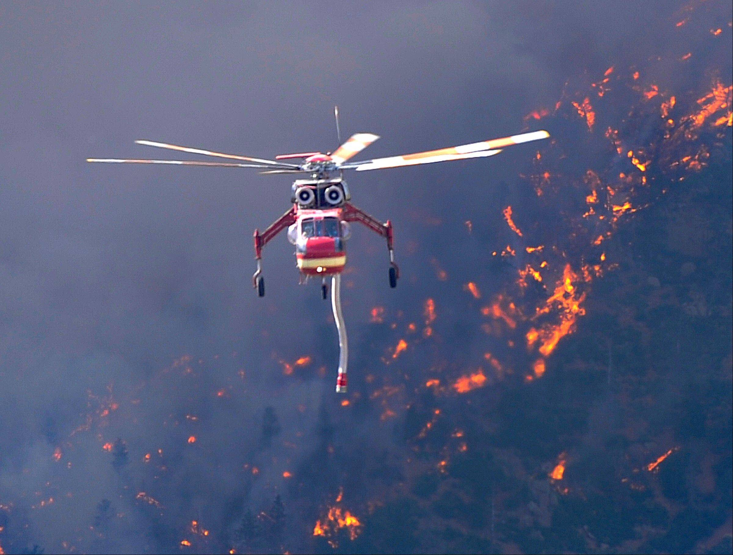 A helicopter returns to Glen Eyrie Reservoir to refill water tanks to fight the Waldo Canyon wildfire Tuesday, June 26, 2012. The Waldo Canyon fire spread to the north as afternoon winds spread embers into the air.