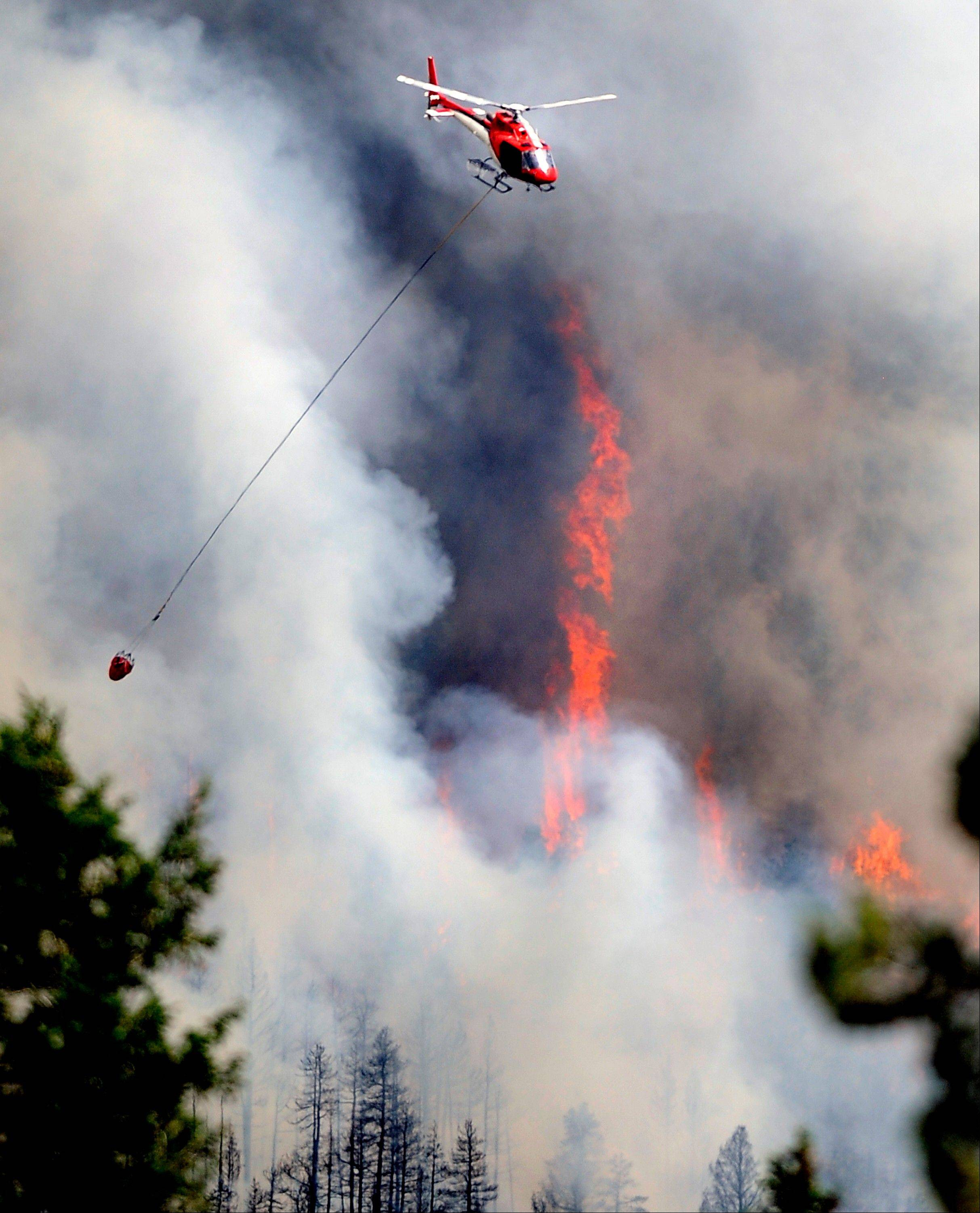 A firefighting helicopter flies above the Flagstaff fire on Tuesday, June 26, 2012 west of Boulder, Colo. Colorado has endured nearly a week of 100-plus-degree days and low humidity, sapping moisture from timber and grass, creating a devastating formula for volatile wildfires across the state and punishing conditions for firefighters.